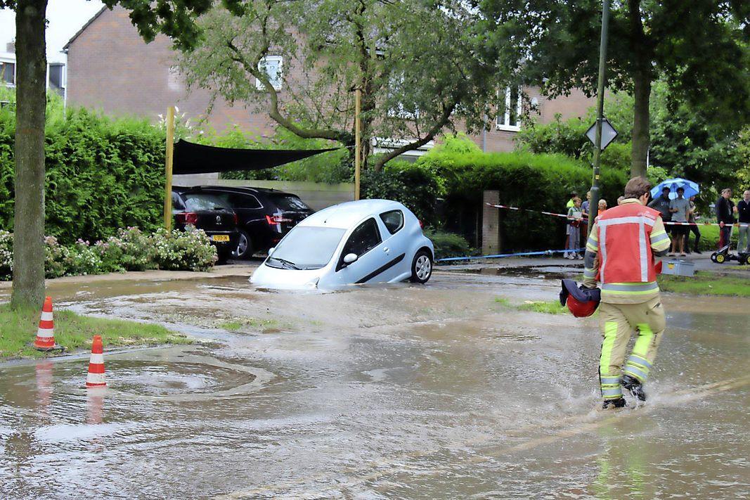 Straat ondergelopen in Naarden door gesprongen waterleiding, auto verdwijnt deels in sinkhole