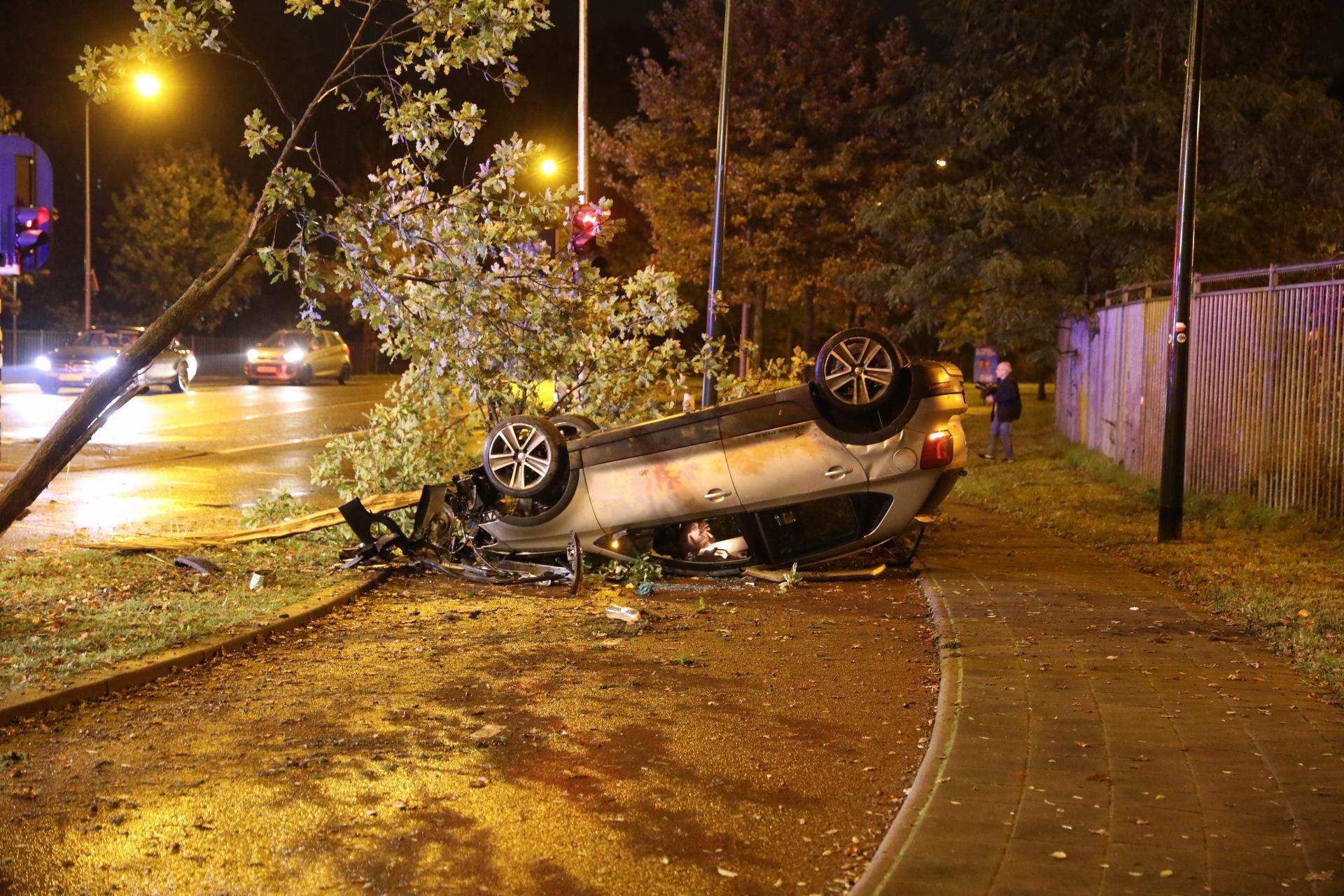 Auto botst tegen boom, slaat over de kop op fietspad bij kruising in Hilversum; drie inzittenden ongedeerd