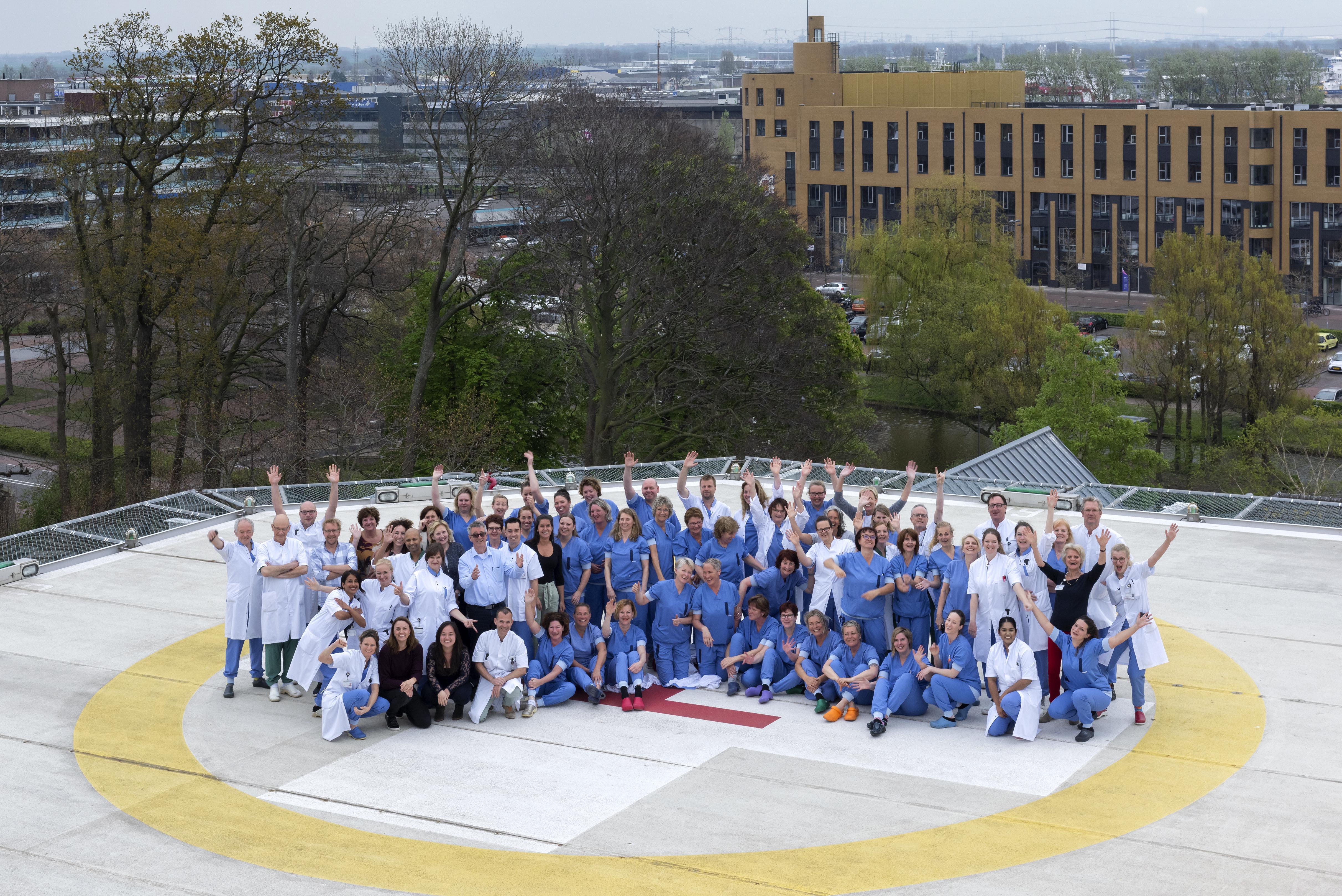 Medewerkers Brandwondencentrum Beverwijk poseren voor viering jubileum op helikopterdek