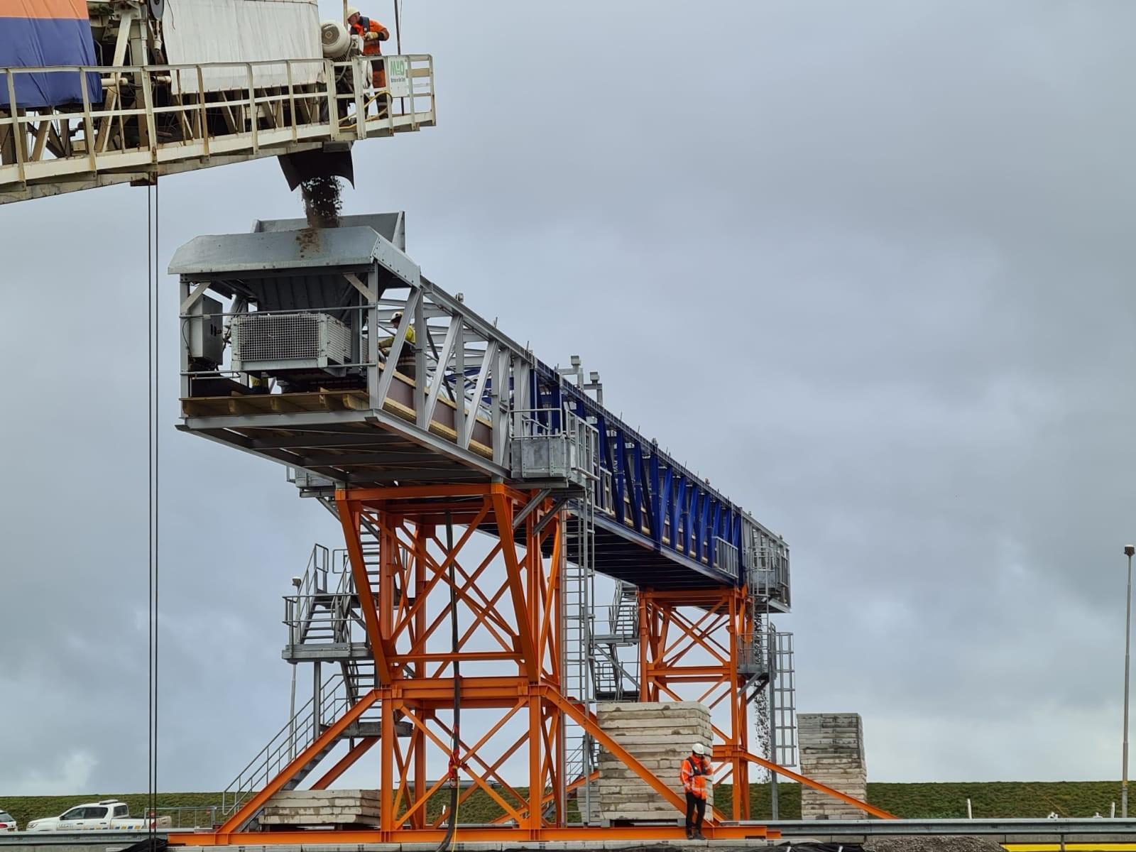Zand voor versterking Afsluitdijk via transportband de snelweg over. Deze methode voorkomt vierduizend scheepsbewegingen langs de sluizen in de dijk