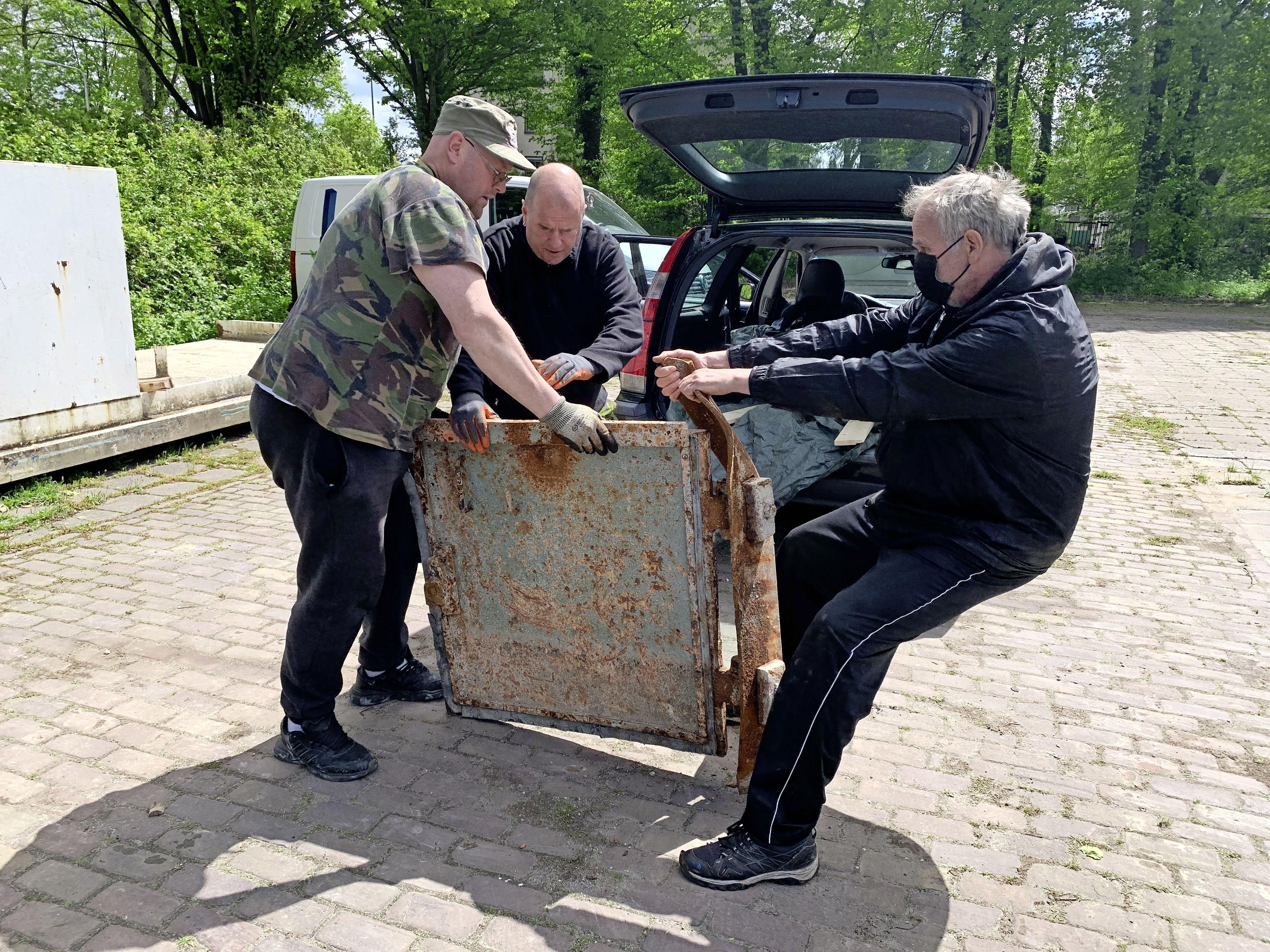Vrijwilligers van de Haagse Bunker Ploeg worstelen met een stalen deur uit de bunker in Driehuis, met slimheid en kracht krijgen ze 'm in de Volvo