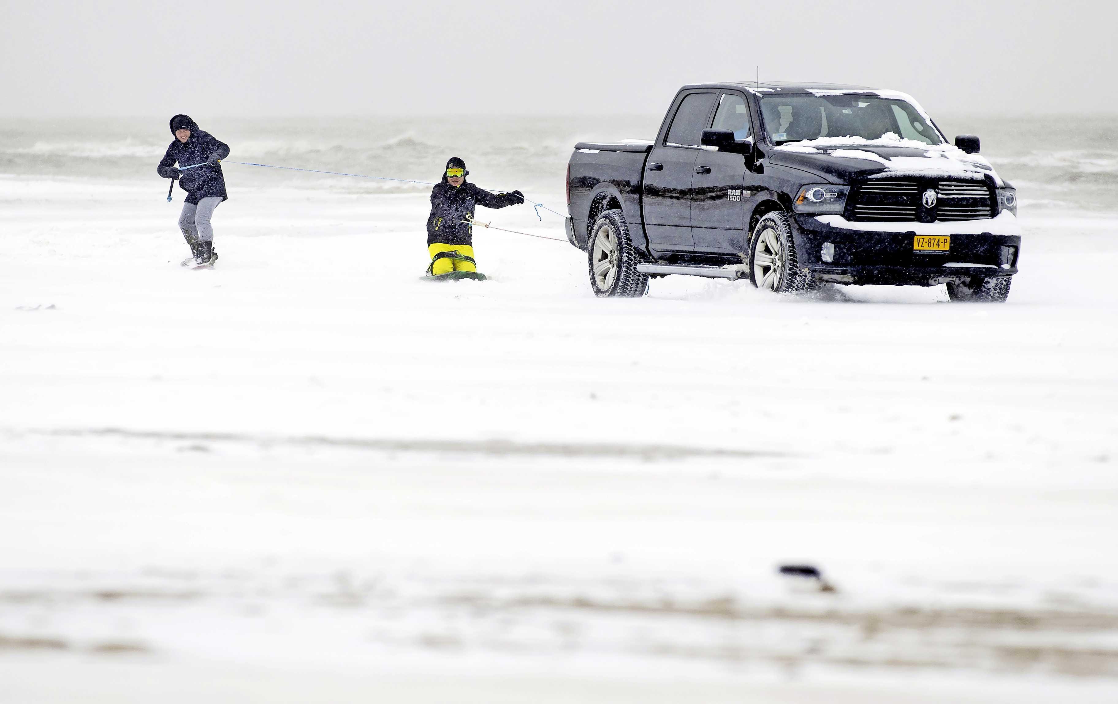 In beeld: snowboarden achter een auto op het strand van Egmond aan Zee
