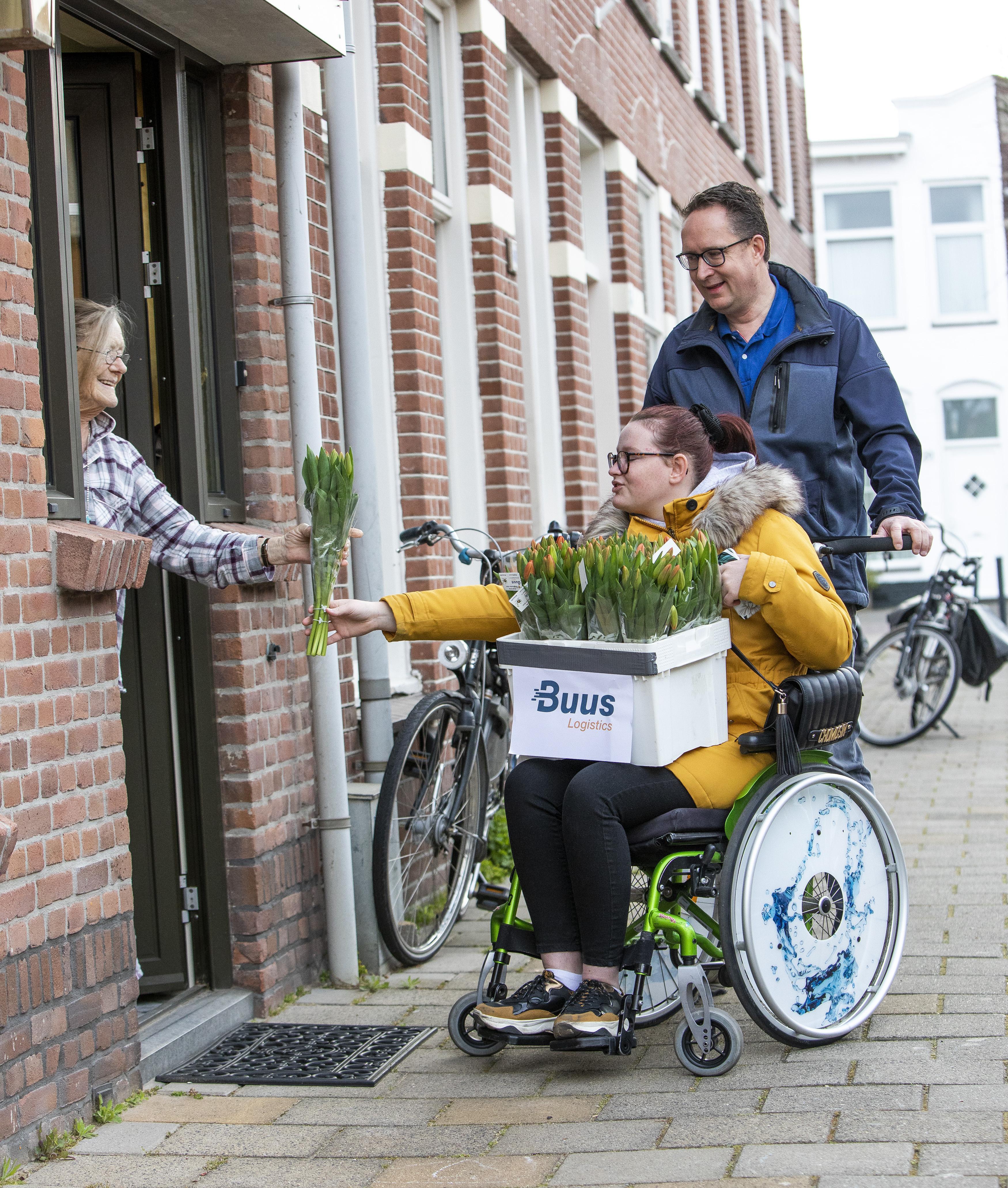 Peter Busscher en dochter Sabrina maken ouderen blij met bosje tulpen in Haarlem-Oost