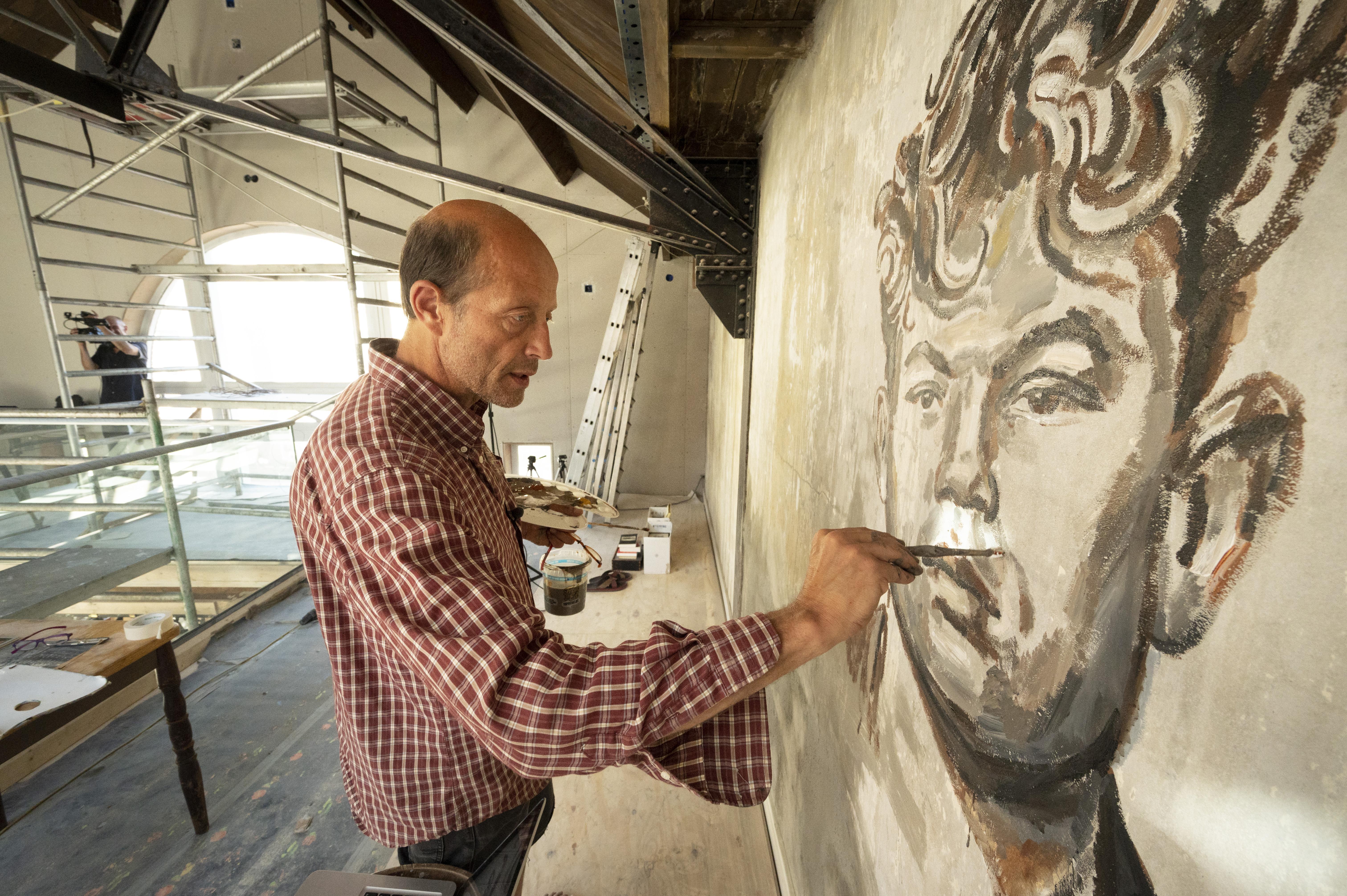 Gijs Donker schildert portret van Marinus van der Lubbe op de muur in Vrijplaats Leiden