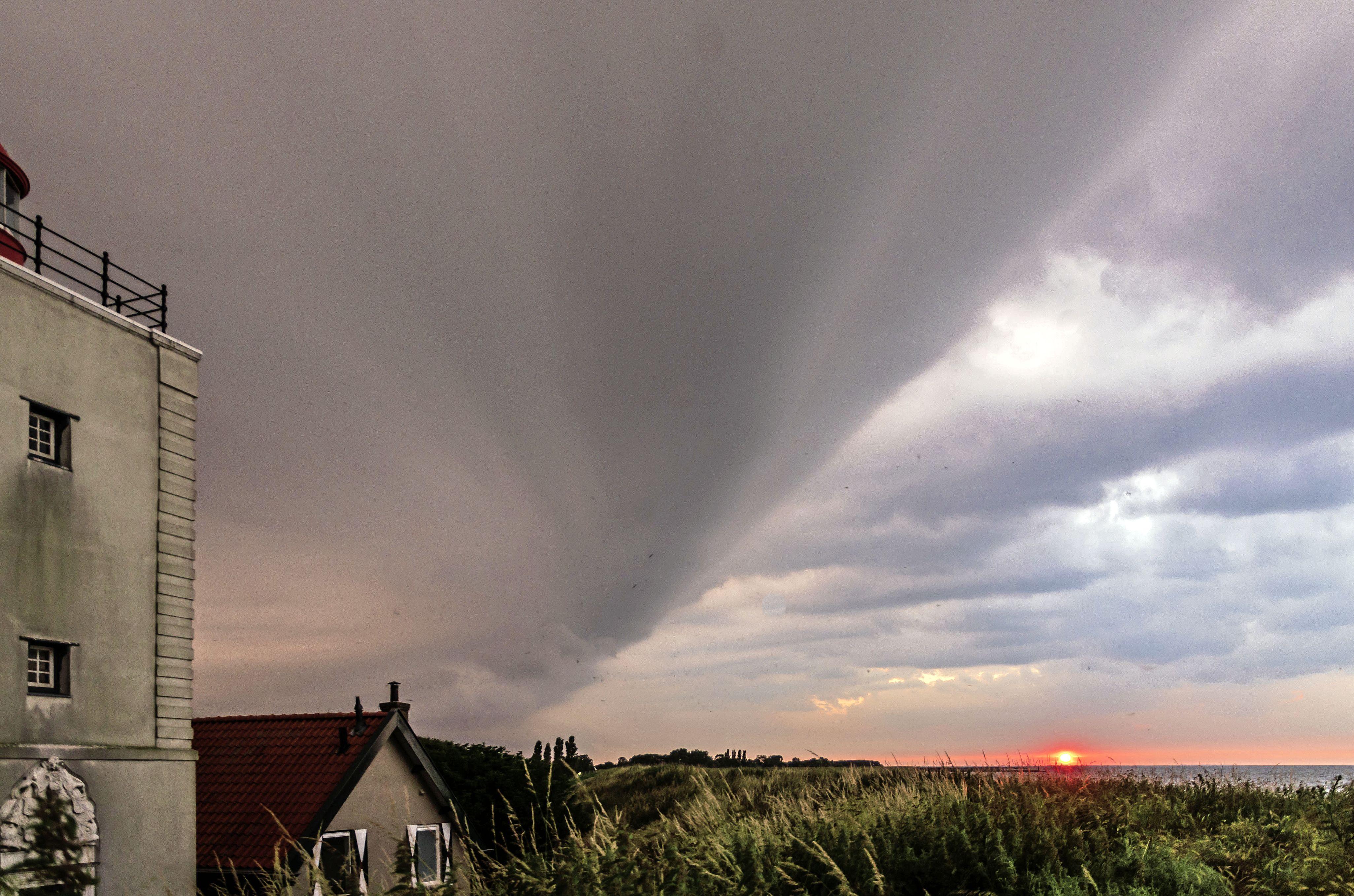 Onweerswolken rollen zich bij ondergaande zon dreigend uit over West-Friesland