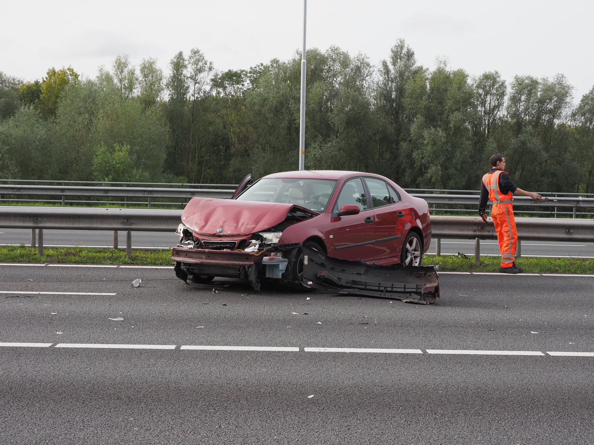 Bestuurder rijdt op A9 bij Velsen-Zuid vangrail in na 'tikje' vrachtwagen; ambulancepersoneel veegt weg schoon