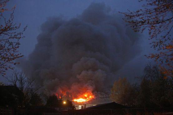 Brandende loods Zwaanshoek ingestort, groep bewoners vluchtte in paniek naar buiten