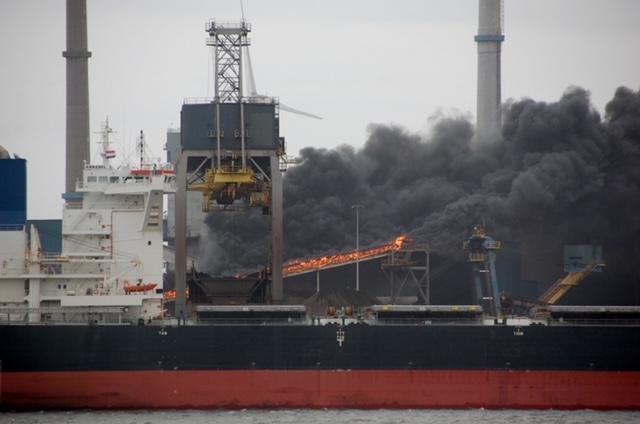 Grote brand bij Tata Steel bij transportband, zwarte wolken in de omgeving, brand tegen einde van de middag geblust [video]
