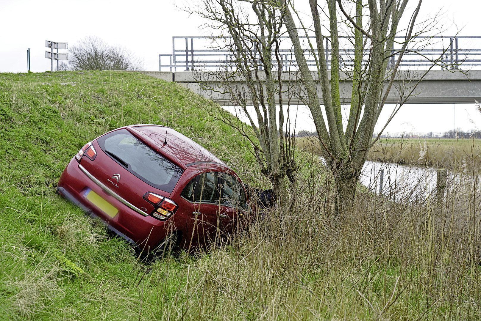 Auto botst tegen dieplader en rijdt de berm in langs Nieuwesluizerweg in Slootdorp