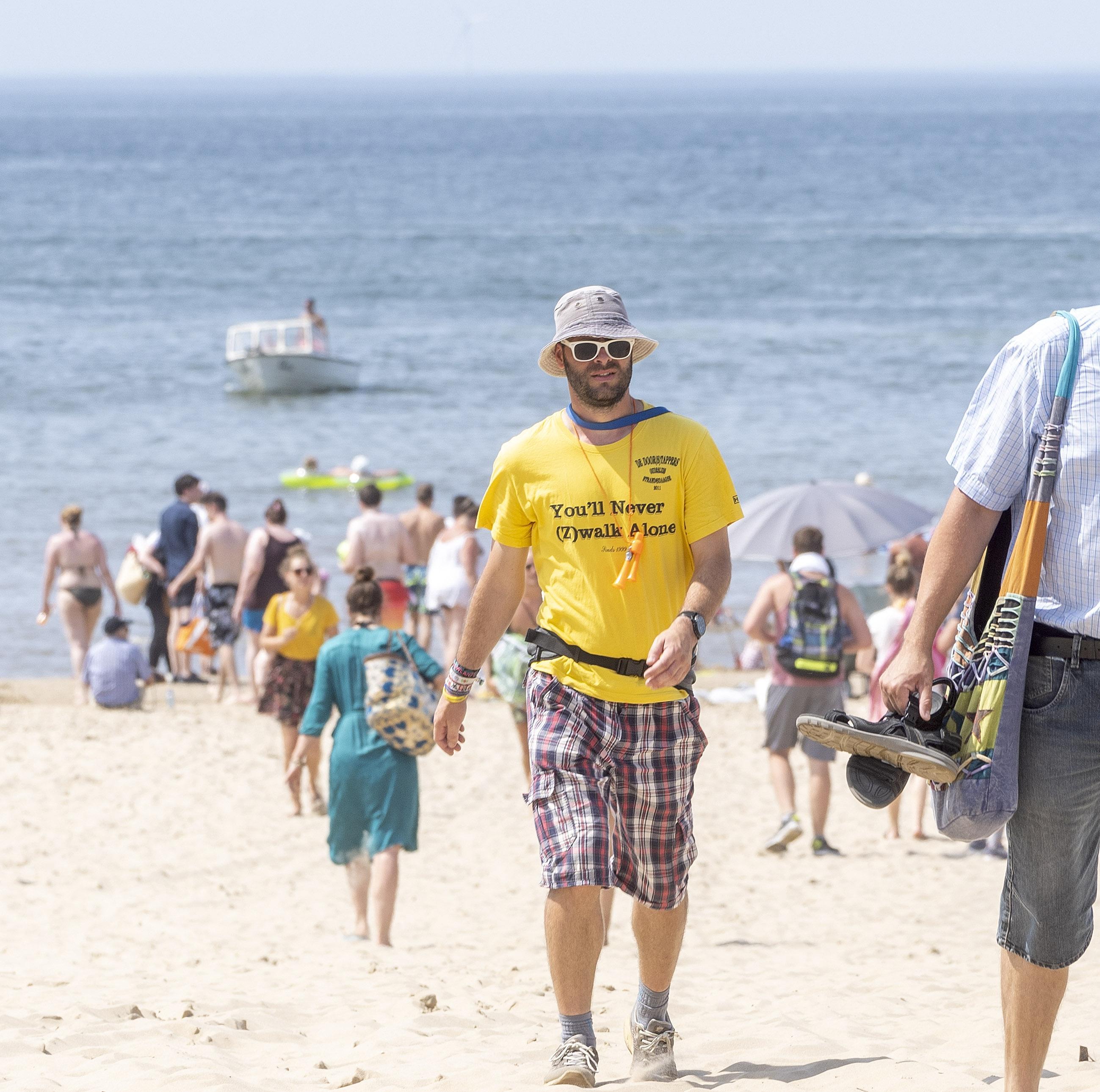 Stoet Strandzesdaagsewandelaars bereikt Egmond aan Zee slalommend met man in djellaba, blaren en wierook