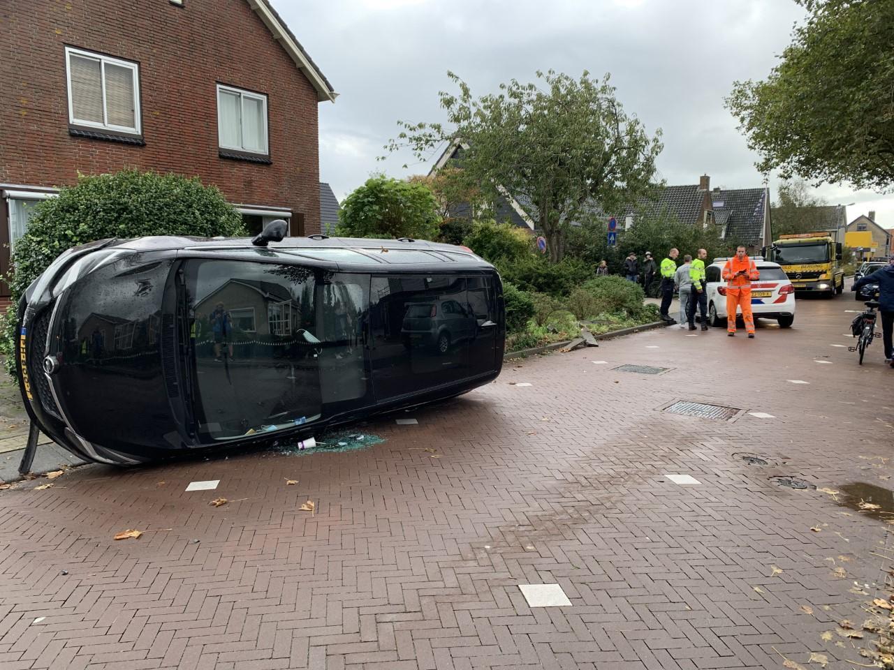 Automobilist rijdt door tuin in Sint Pancras; auto op de zijkant tot stilstand
