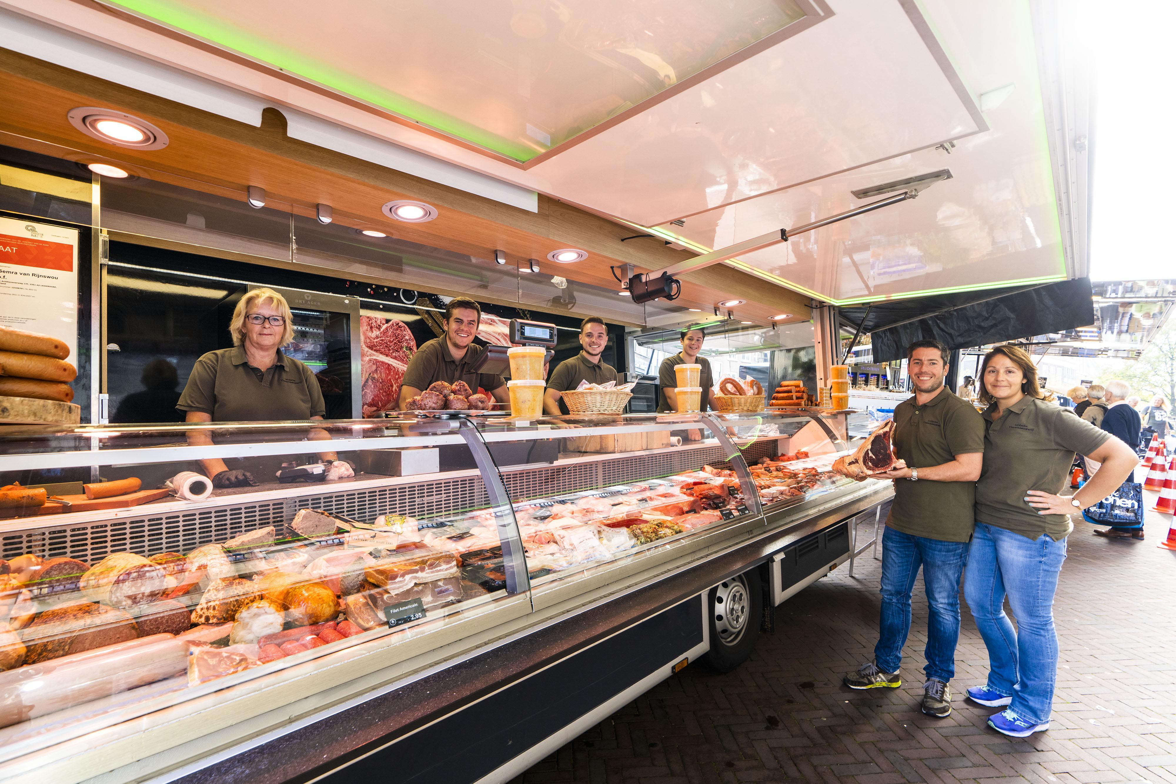 Semra en Richard van Rijnswou van de Leidsche Vleeschhouwerij hangen met hun eerste jubileum op de markt een rijpkast in hun wagen