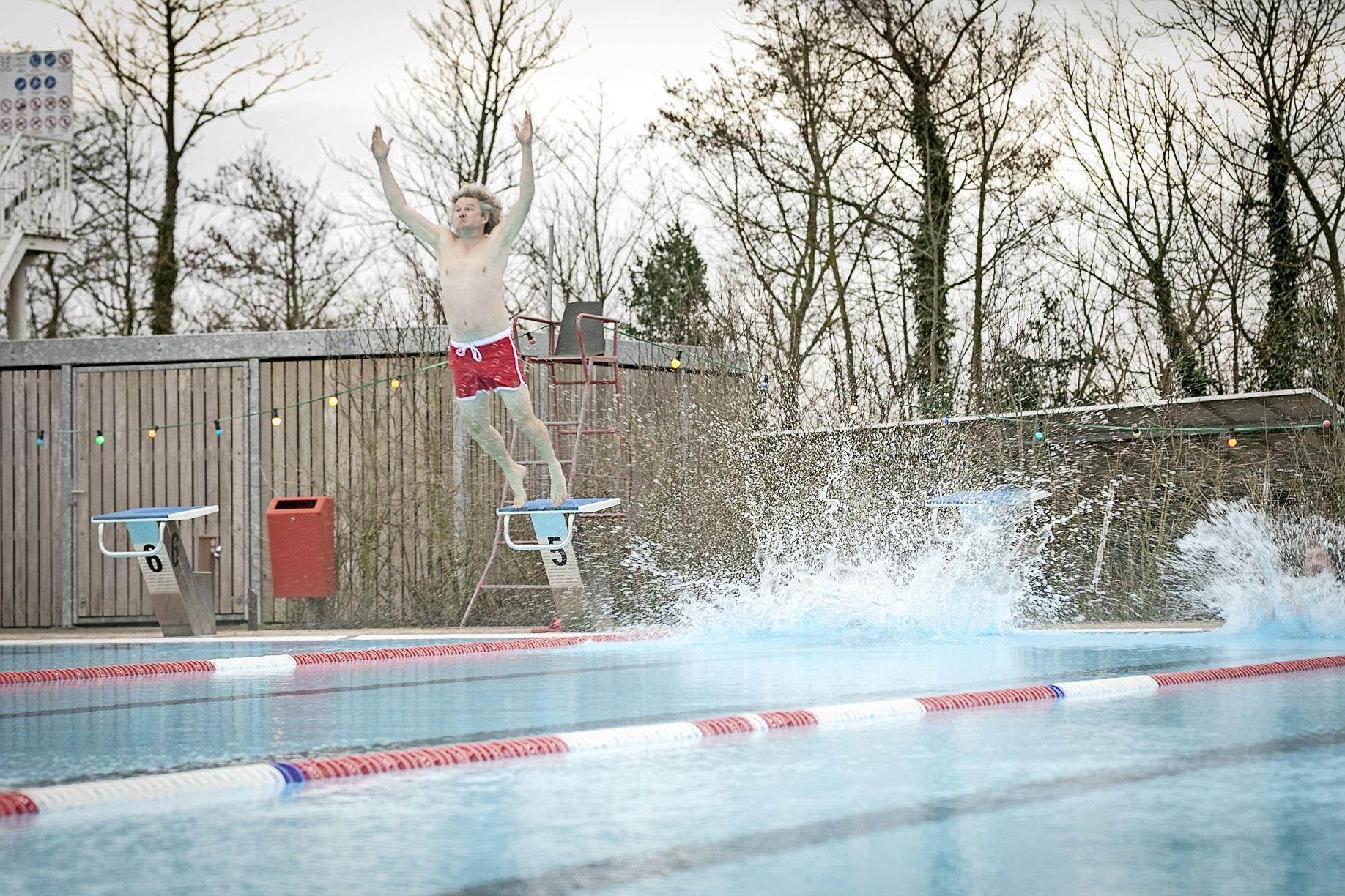 Met een reuzensprong opent wethouder Remko van de Belt zwembad Molenkoog. Gevoelstemperatuur: enkele graden boven nul