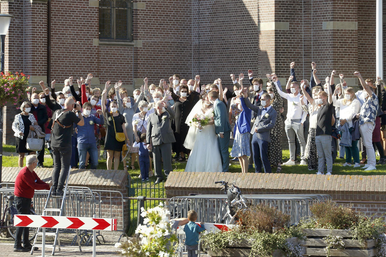 Mondkapjes op voor groepsfoto na sluiten van huwelijk