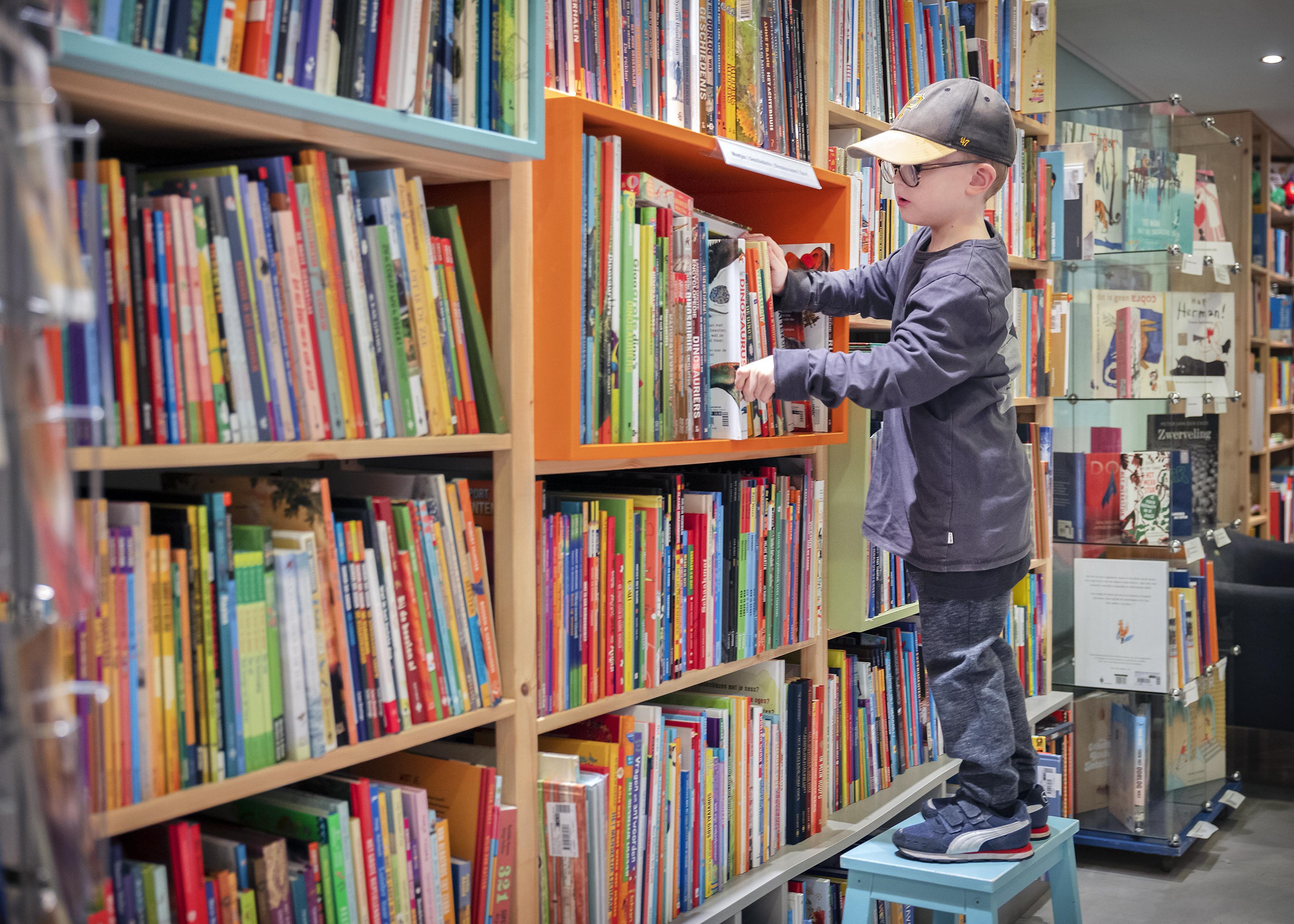 Geduldig wachten op bankje bij boekwinkel Kiekeboek in Haarlem; veel kinderen gaan in coronatijd meer lezen