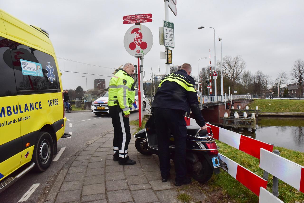 Botsing tussen scooter en fietser op Kanaalweg in Leiden, één bestuurder afgevoerd naar ziekenhuis