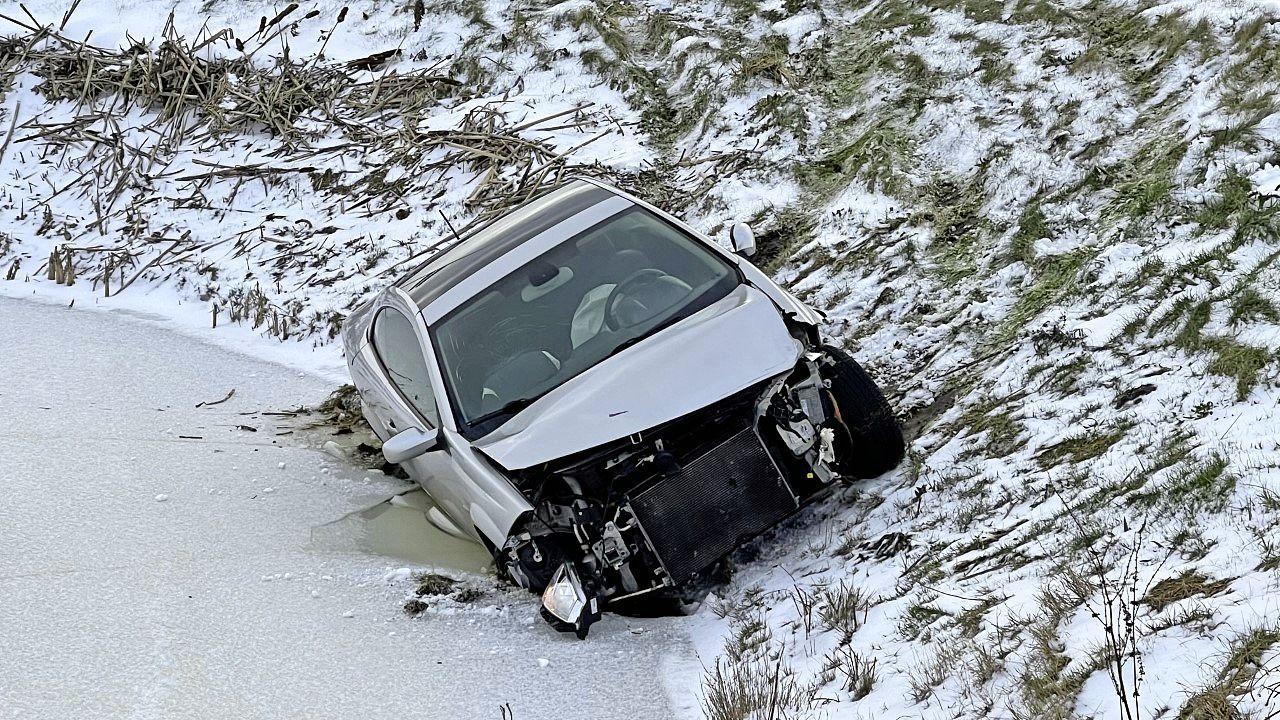 Auto belandt met wielen in Obdamse sloot, ijs voorkomt dat voertuig volledig in water glijdt