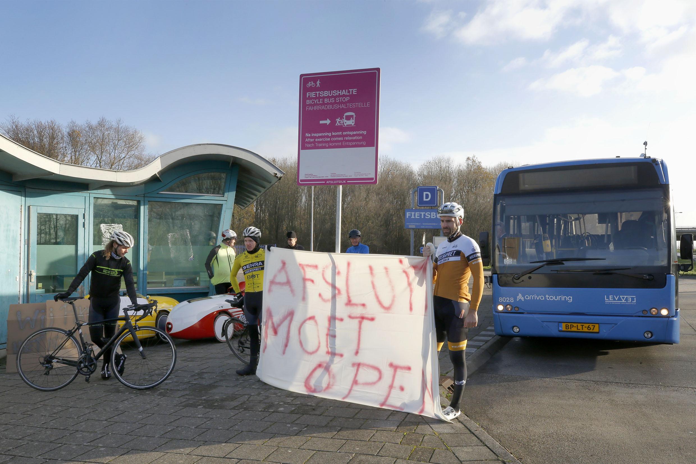 'Afsluitdijk moet open'. Spandoeken en protestborden bij de halte van de pendelbus in Den Oever. Fietsers protesteren tegen langere afsluiting pad over dijk