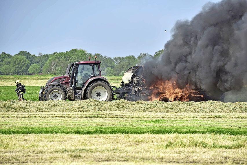 Flinke vlammen en veel rook bij brandende balenpers in weiland Rijpwetering