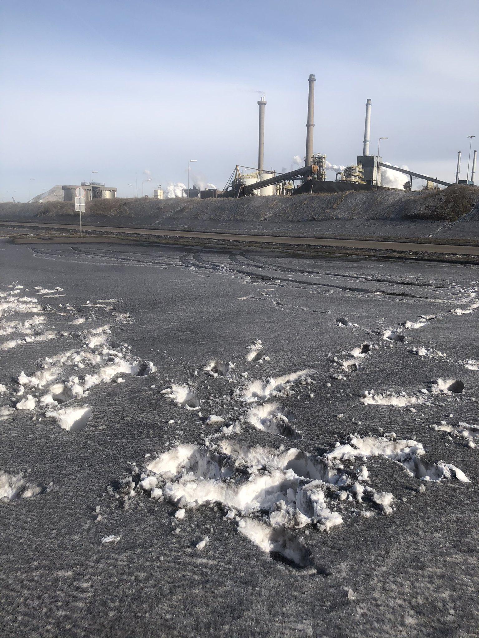 Zwarte sneeuw bedekt wegen en duinen nabij Tata Steel IJmuiden