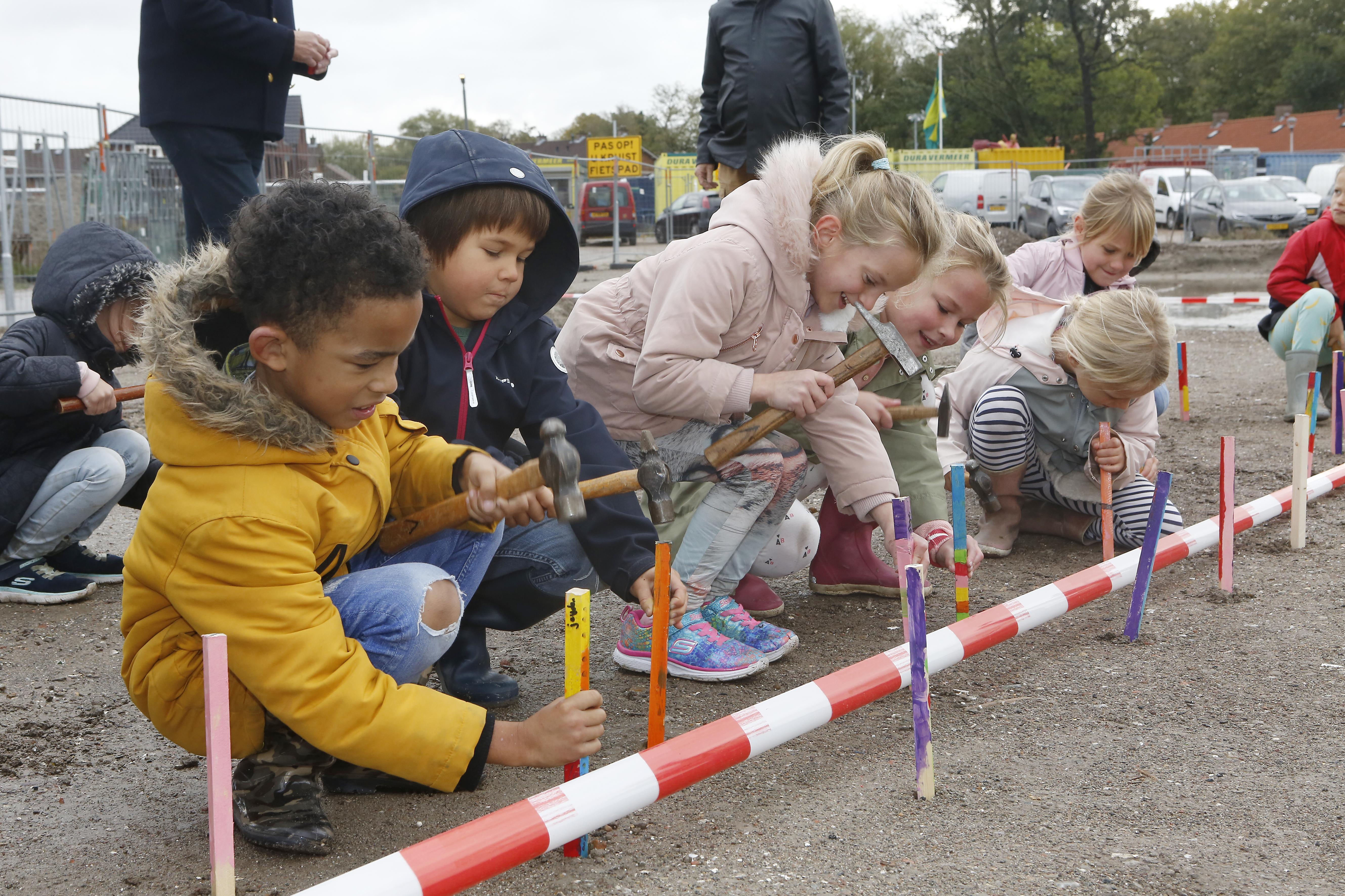 Leerlingen PC Hooftschool uit Muiden timmeren met plezier de piketpaaltjes voor hun nieuwe schoolgebouw de grond in; IKC Muiderkring moet begin 2022 de deuren openen