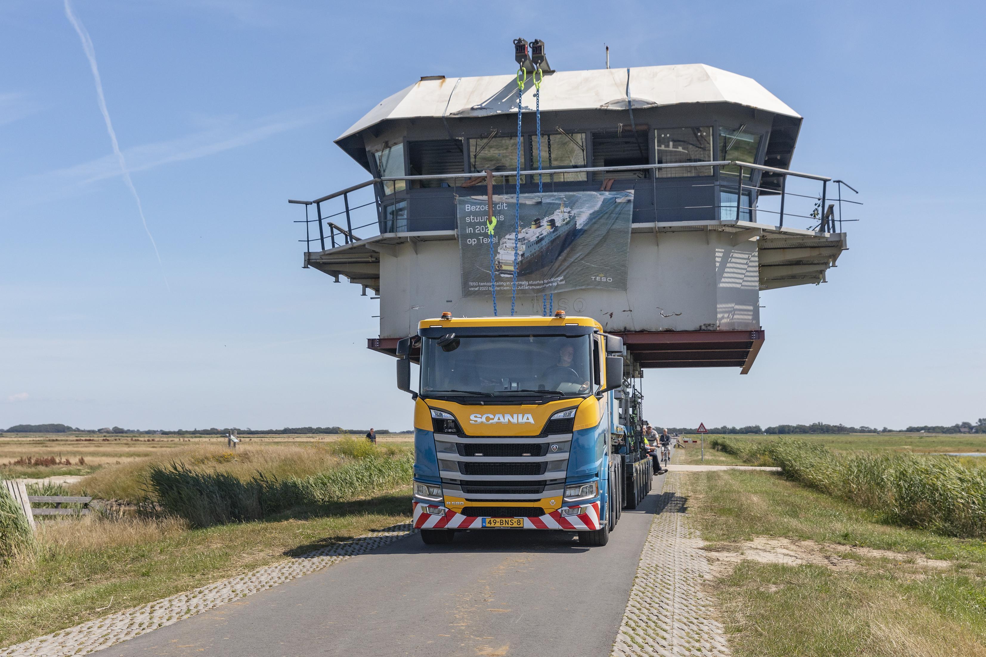 Als een rijdend flatgebouw schrijdt het enorme stuurhuis van veerboot Schulpengat over Texel. 'Een spannende klus', die veel bekijks trekt