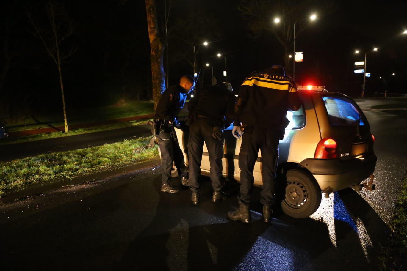 Auto knalt tegen boom in Huizen na politieachtervolging
