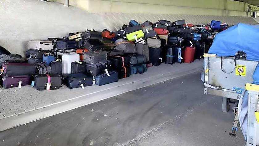 Op Schiphol liggen de koffers zelfs onder het viaduct door grote storing