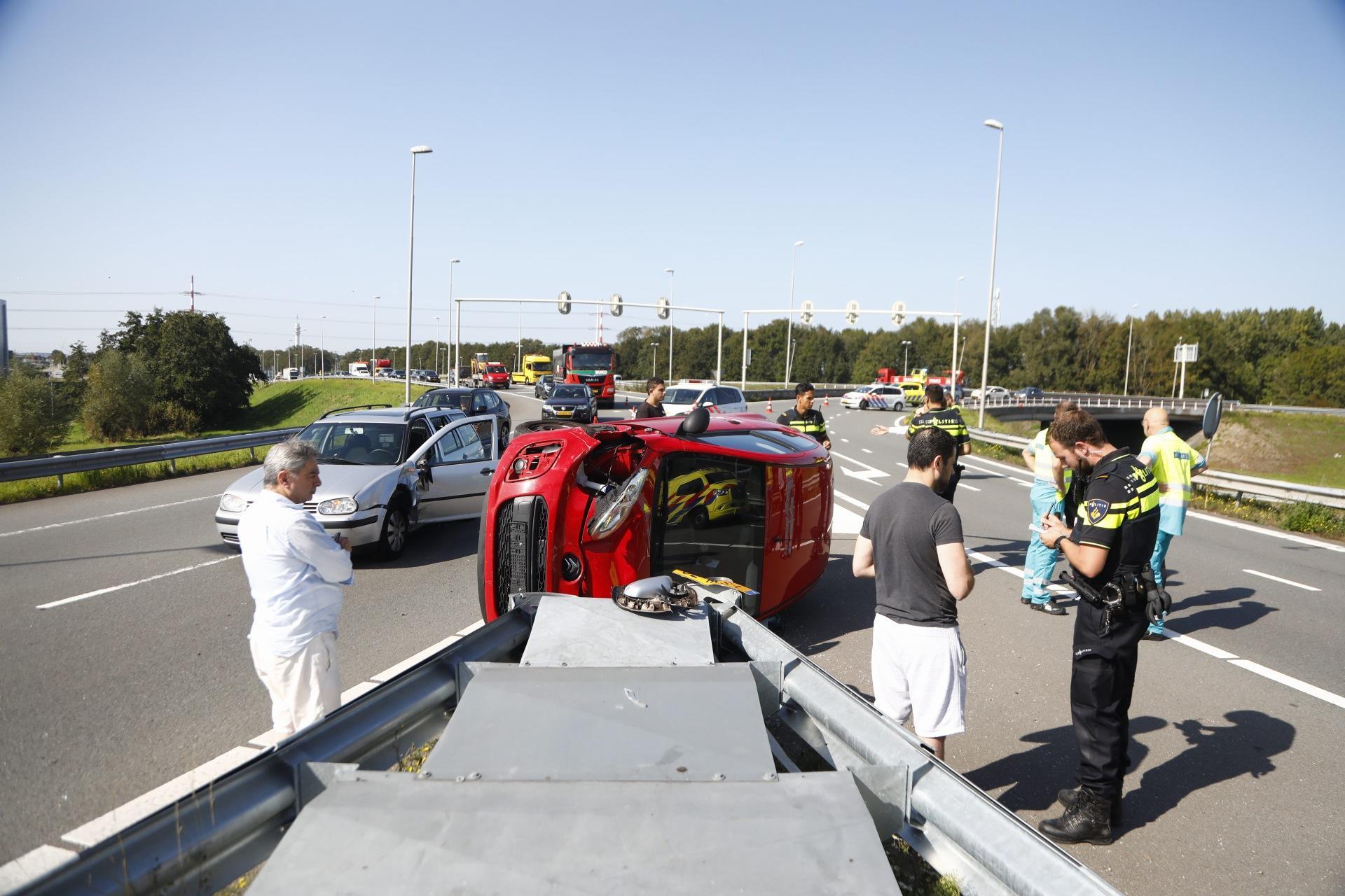 File rond knooppunt Rottepolderplein na ongeluk, waarbij auto kantelt