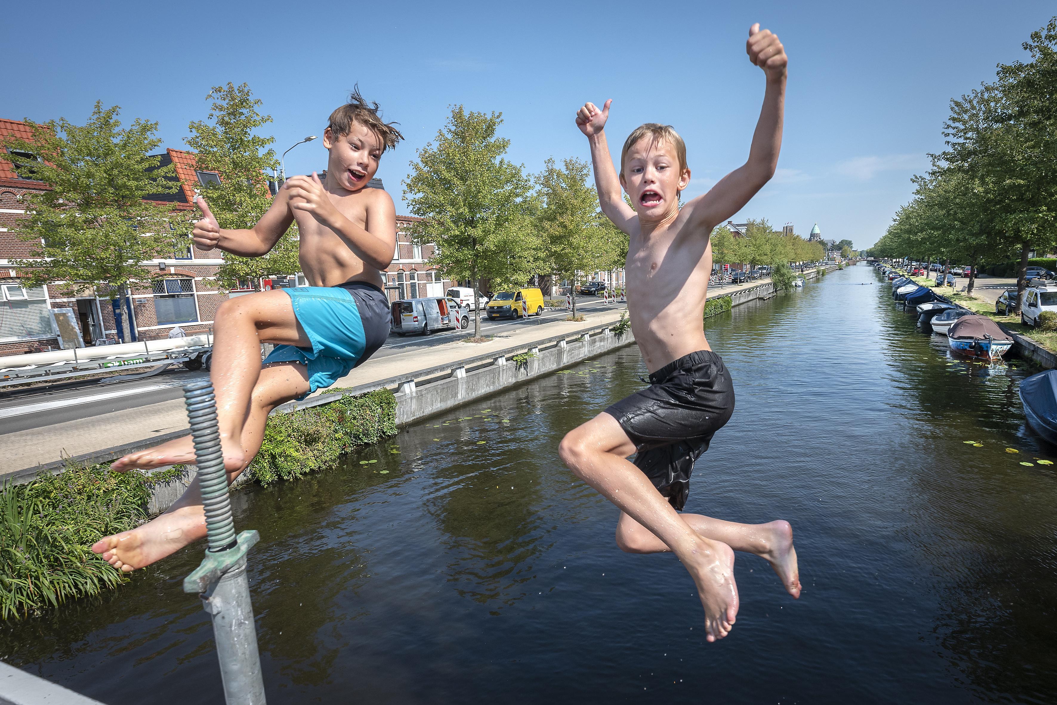 Haarlemse brugspringertjes genieten van verkoeling en waarschuwen elkaar bij naderende bootjes