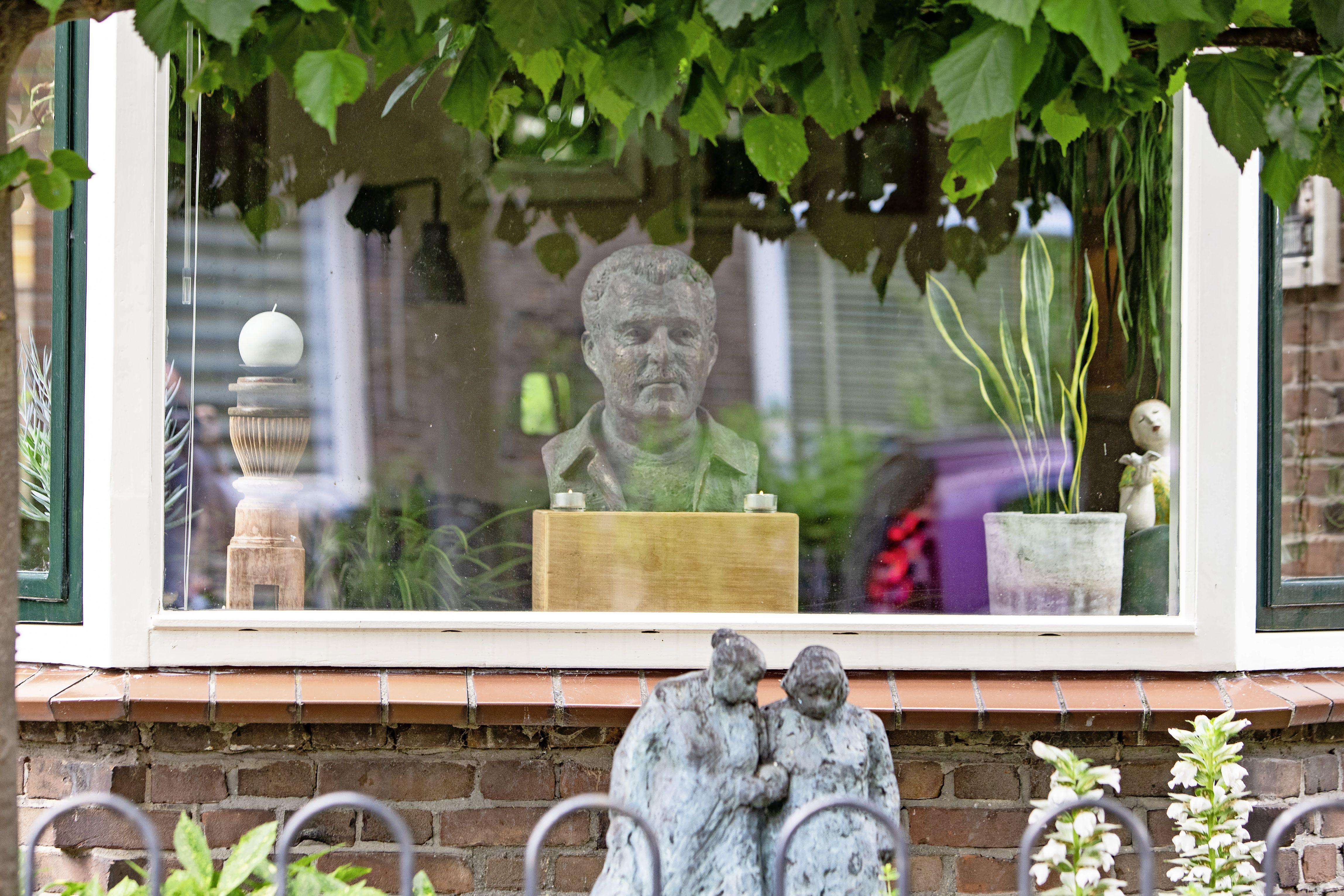 Peter R. de Vries kijkt uit over de Baarnse Mauvestraat, met een kaarsje links en een kaarsje rechts; Klein eerbetoon van beeldhouwster Nieneke Lamme, die de misdaadbestrijder in brons vereeuwigde