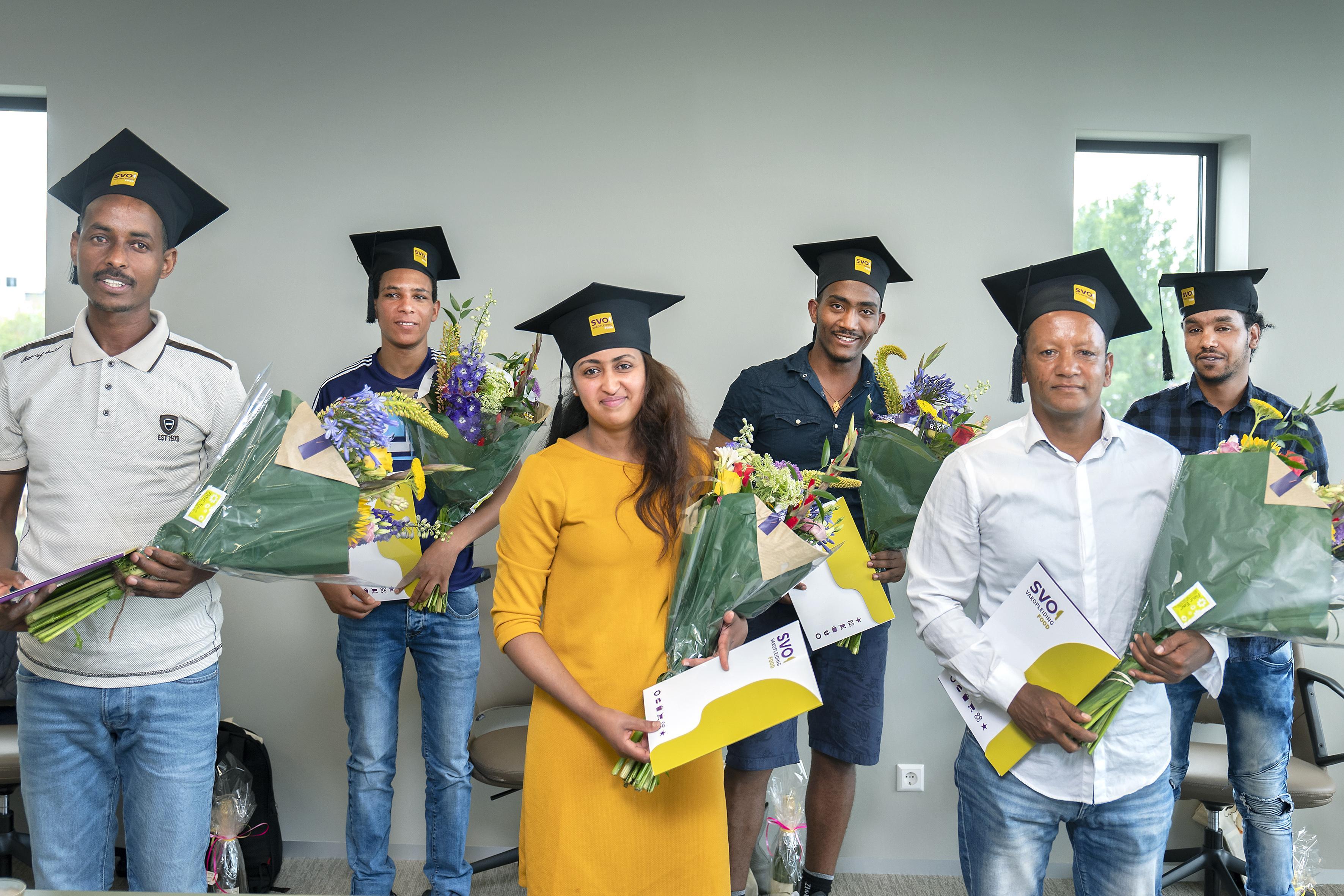 Glunderende statushouders ontvangen in Haarlem 'medewerker voedingsindustrie'-diploma bij spekjesfabriek