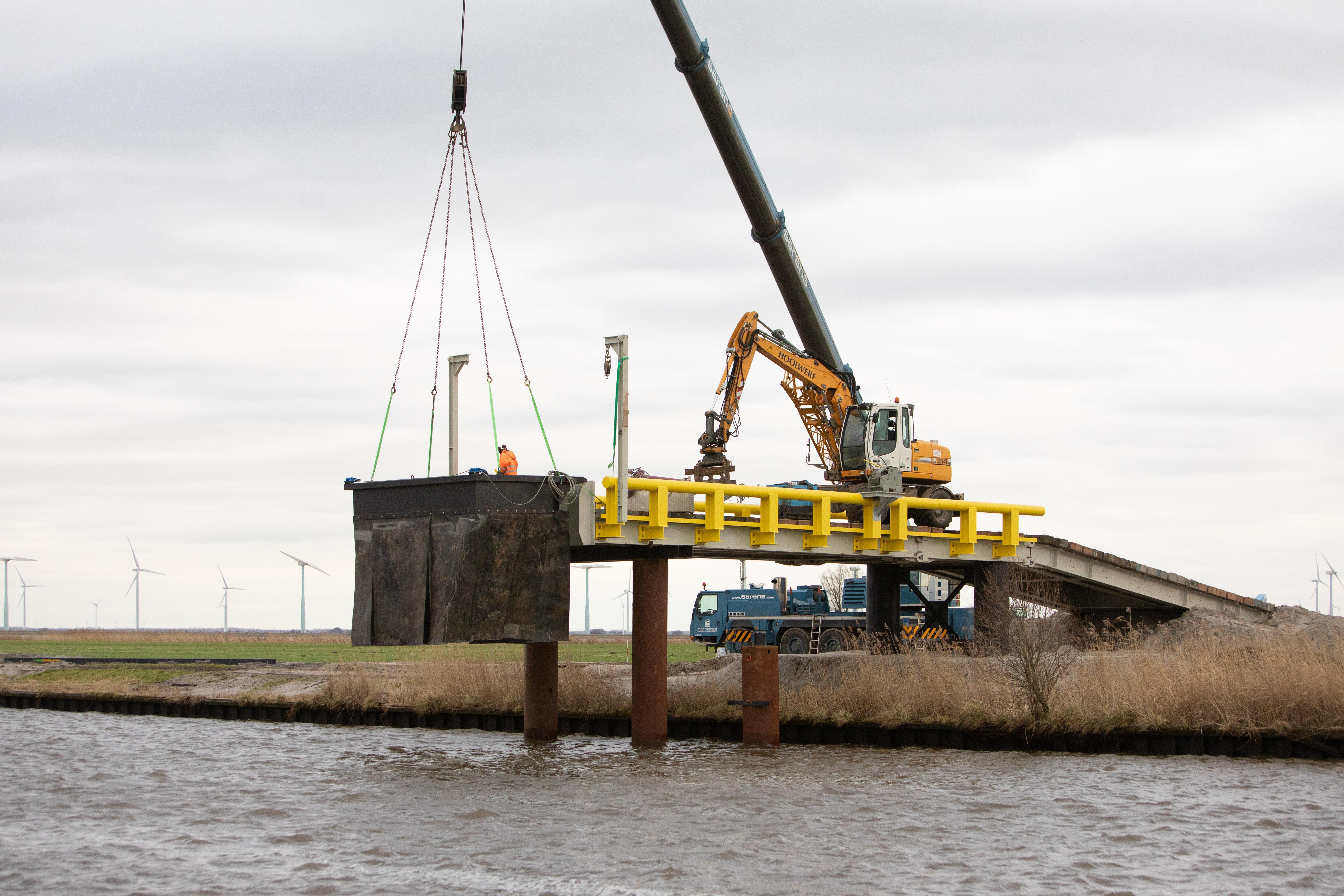Tijdelijk laad- en losperron in de monding van de Eem voor afvoer van 40.000 vrachtwagenladingen aan vervuilde grond Westdijk bij Spakenburg; Vrachtwagens over noodweg door de weilanden