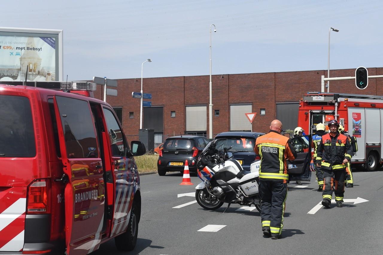 Vrachtwagen rijdt achteruit bij stoplicht en raakt auto in Leiderdorp; chauffeur rijdt door