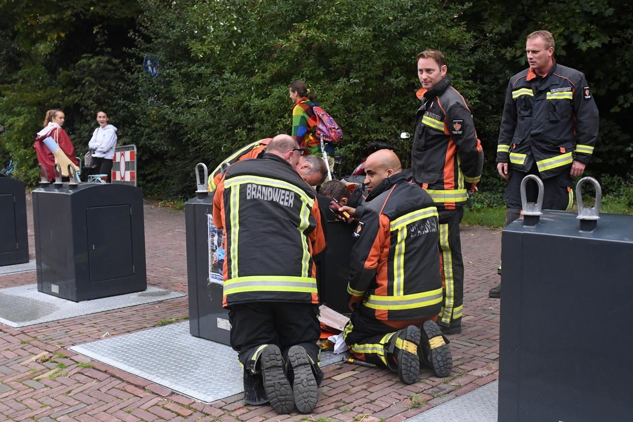 Vrouw gooit per ongeluk tasje weg in container; brandweer komt met zes man in actie