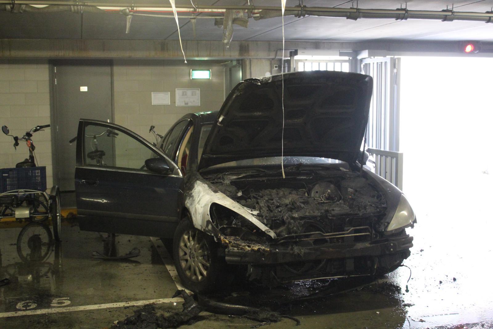Auto vat vlam in parkeergarage in Huizen