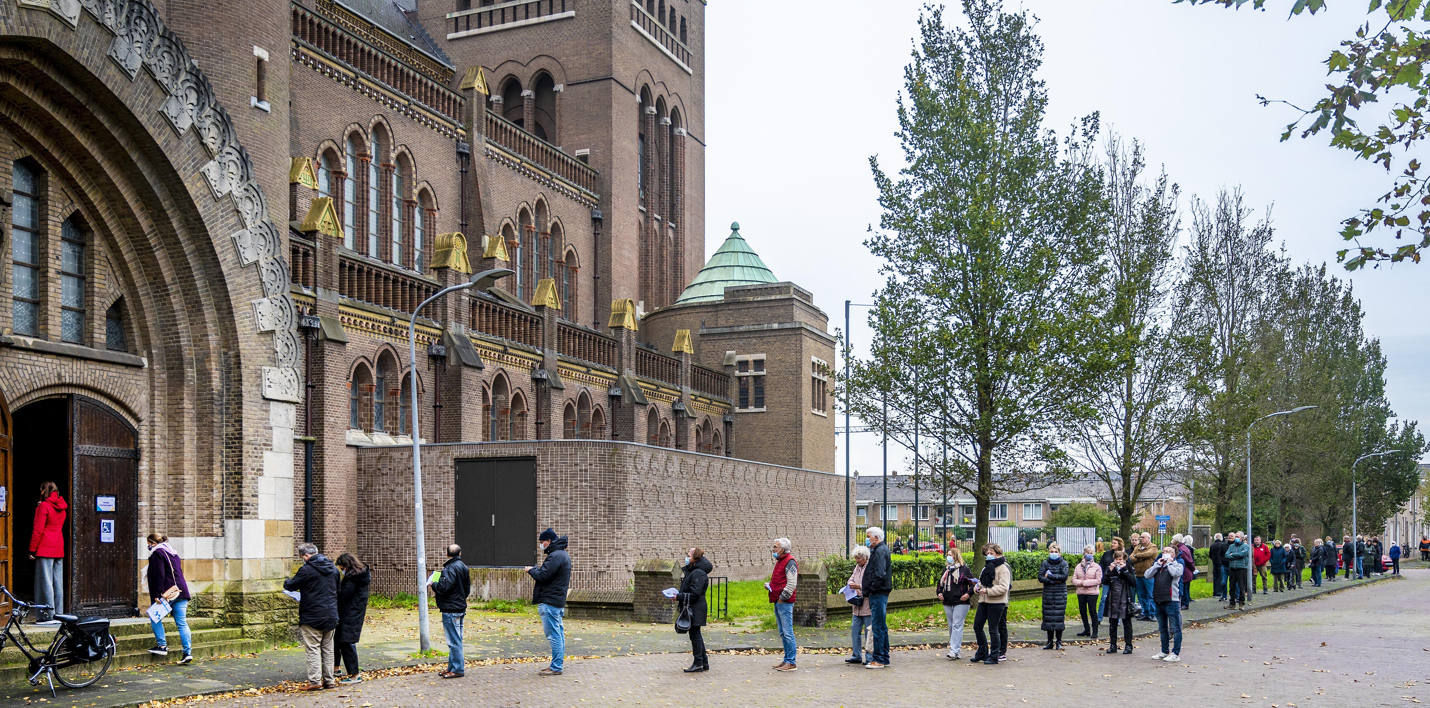 Drie kwartier in de rij rond de Bavo in Haarlem voor de griepprik: 'Het lijkt de Efteling wel, alleen de bordjes ontbreken'