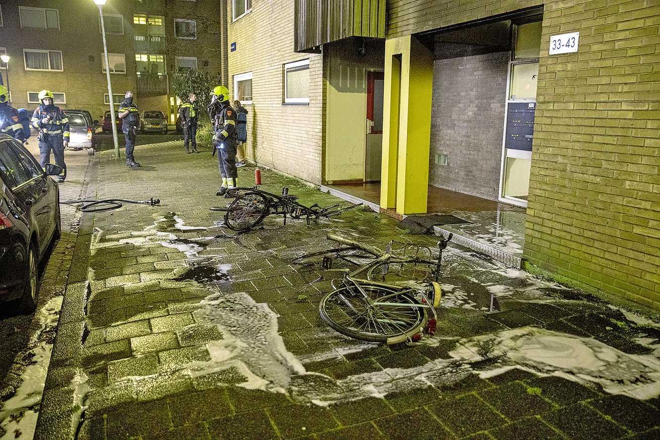 Scooter en fietsen branden uit tegen gevel in Haarlem, woningen uit voorzorg geëvacueerd, politie houdt twee verdachten aan