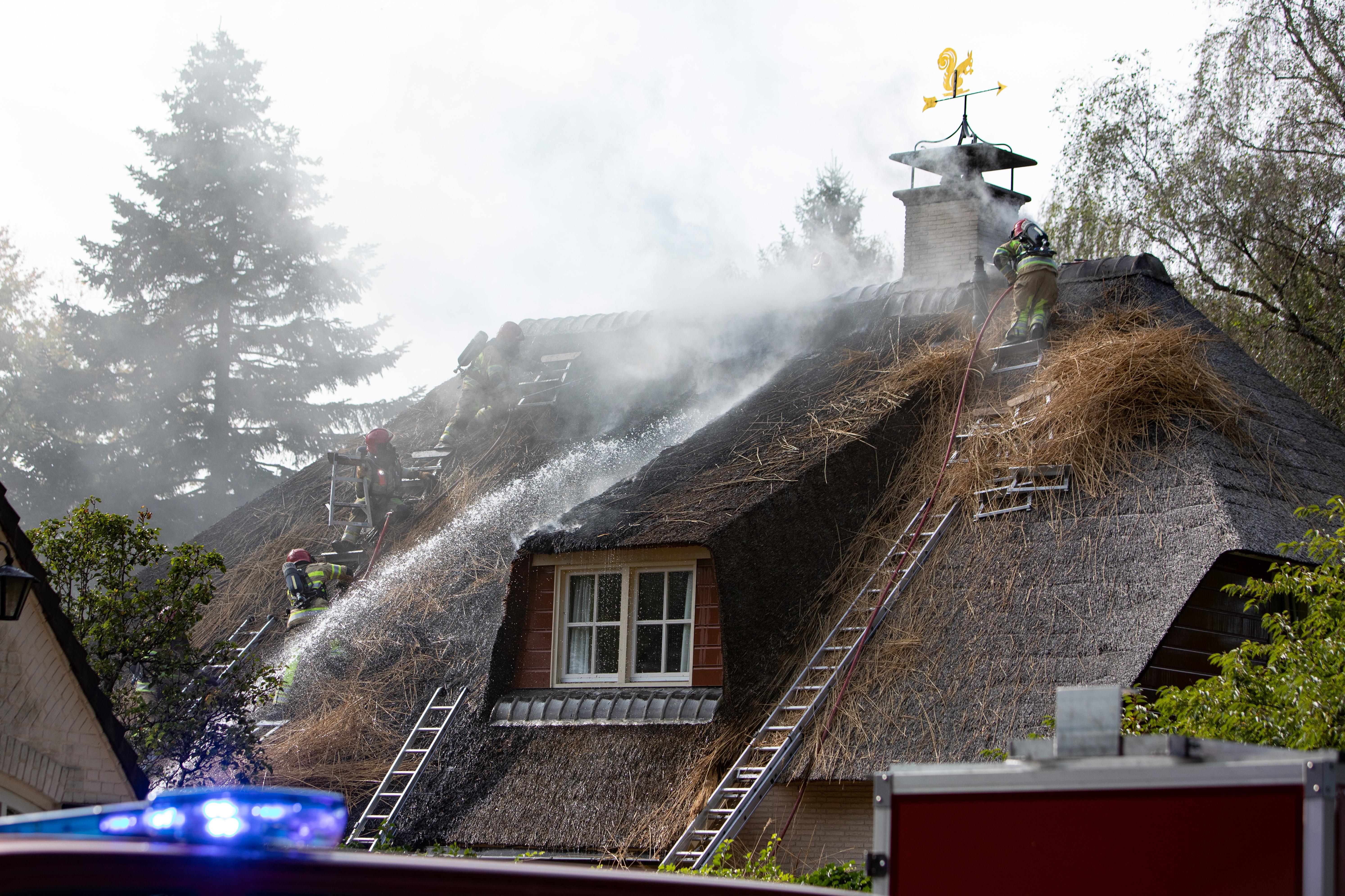 Schilders gaan vuur te lijf met een tuinslang om erger te voorkomen. Uitslaande brand verwoest rieten kap van Blaricumse villa
