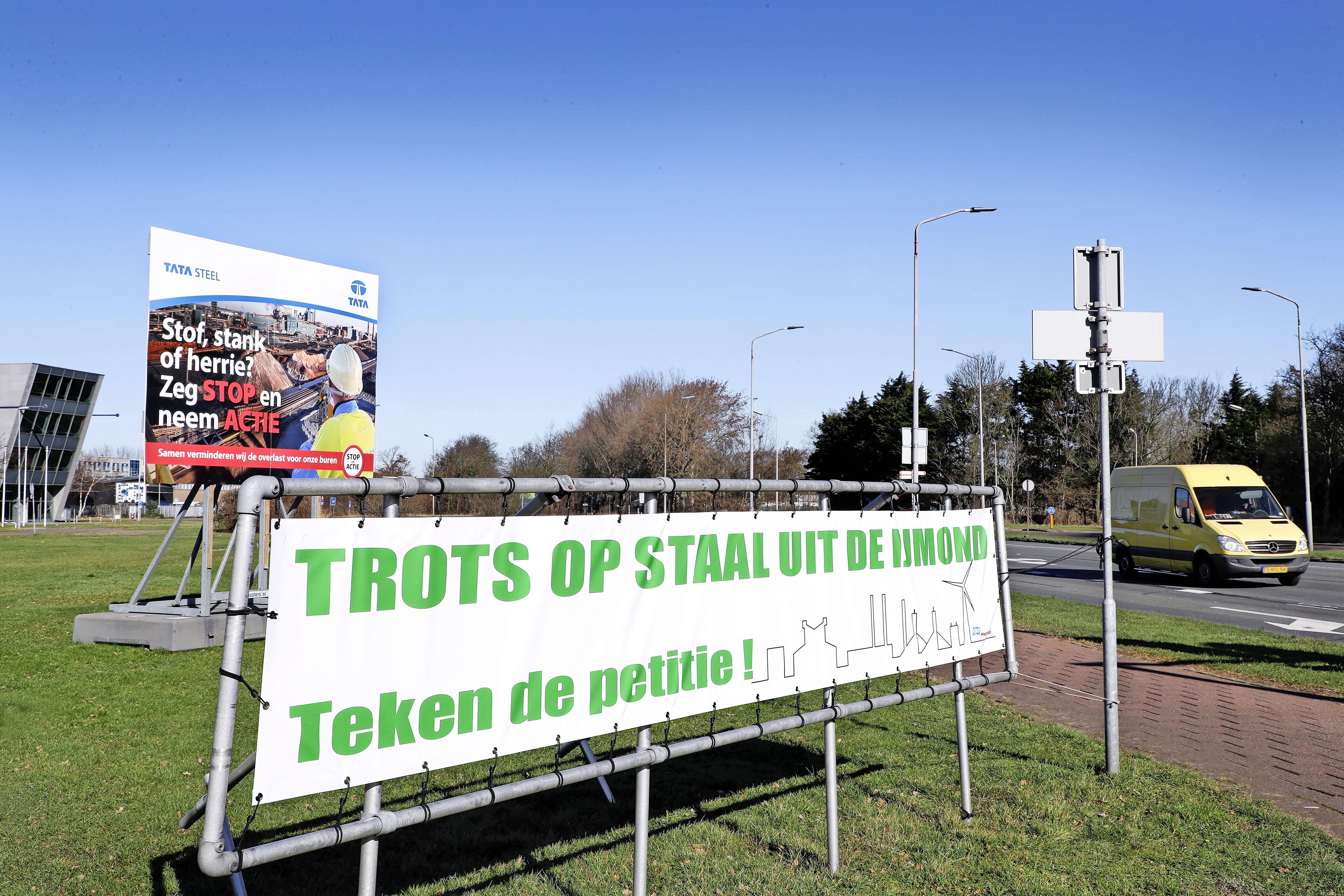 Een levensgroot spandoek met de oproep de petitie te tekenen voor behoud Tata Steel staat vlak bij ingang