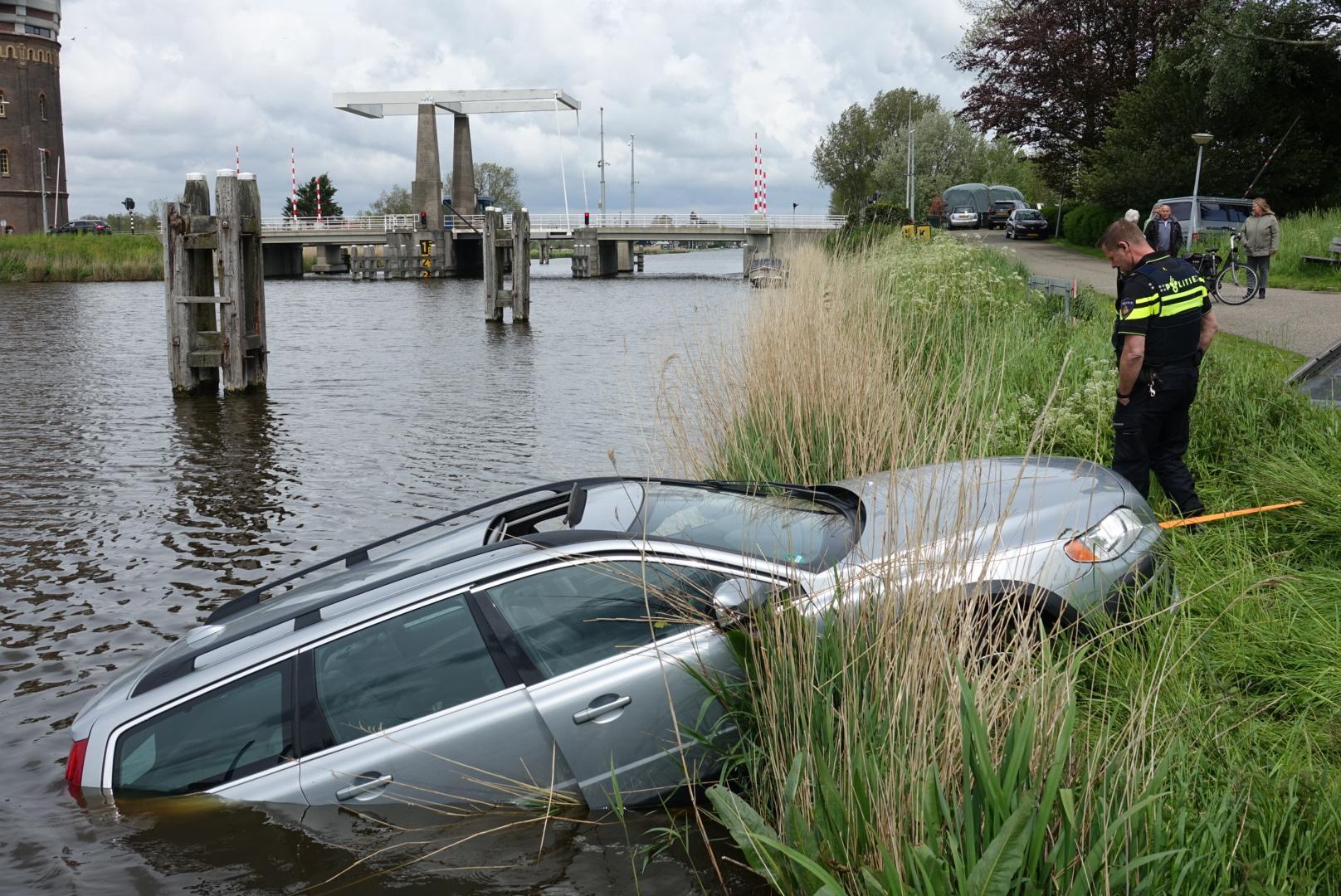 Inzittende van te water geraakte auto klimt door dakraam naar buiten in Westzaan