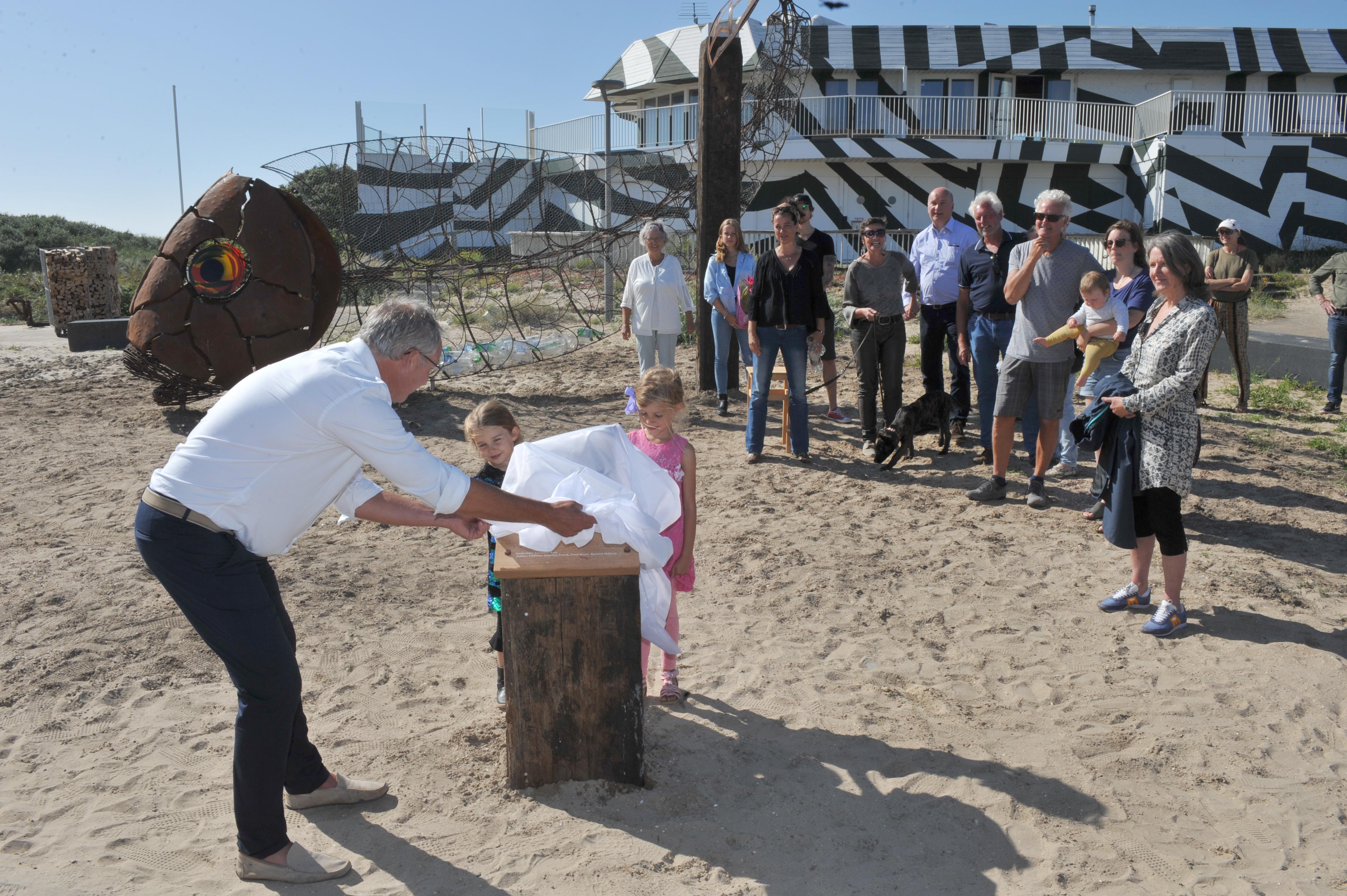 Plastic vangen met een grote vis op strandplateau Castricum