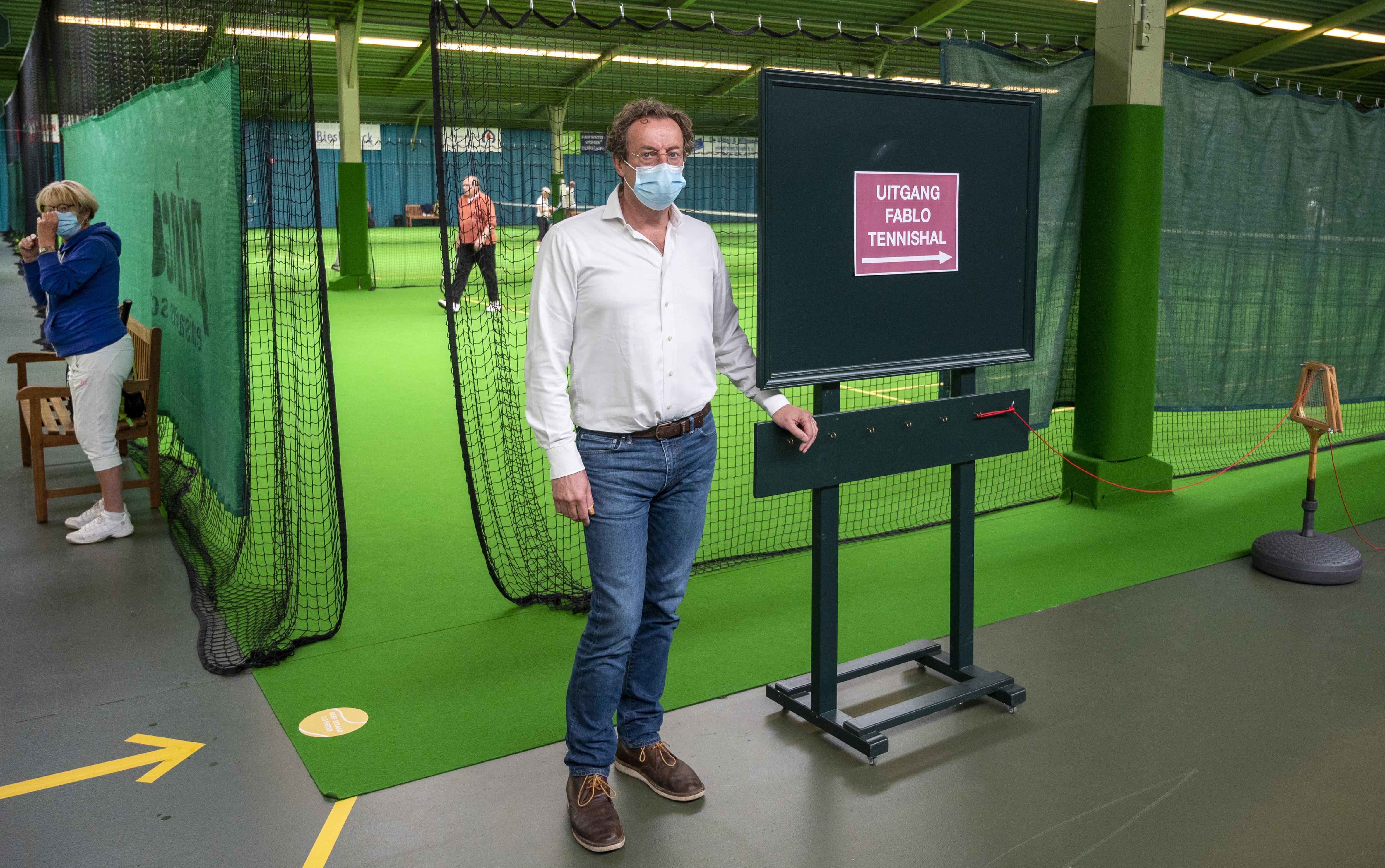 Tennissen anno corona in Fablo Tennishal in Haarlem: met een racket de deur openen en met mondkapje naar je plaats