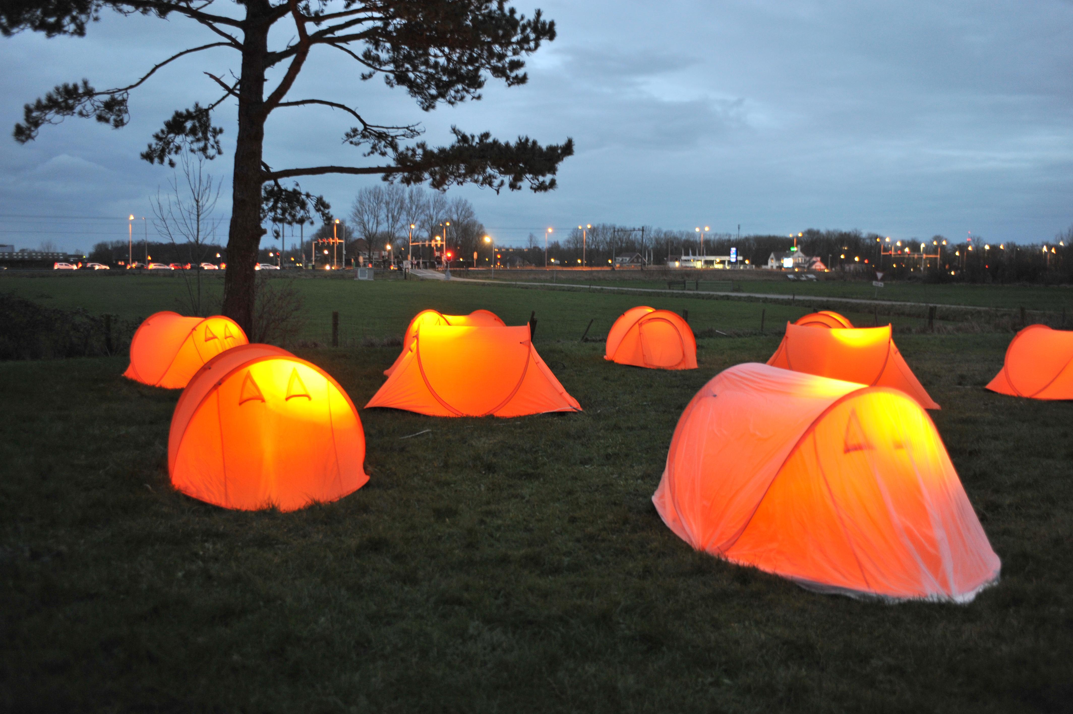 Tien verlichte tentjes als lampionnen in het veld bij Uitgeest: over vrolijkheid en diepe ellende tegelijk
