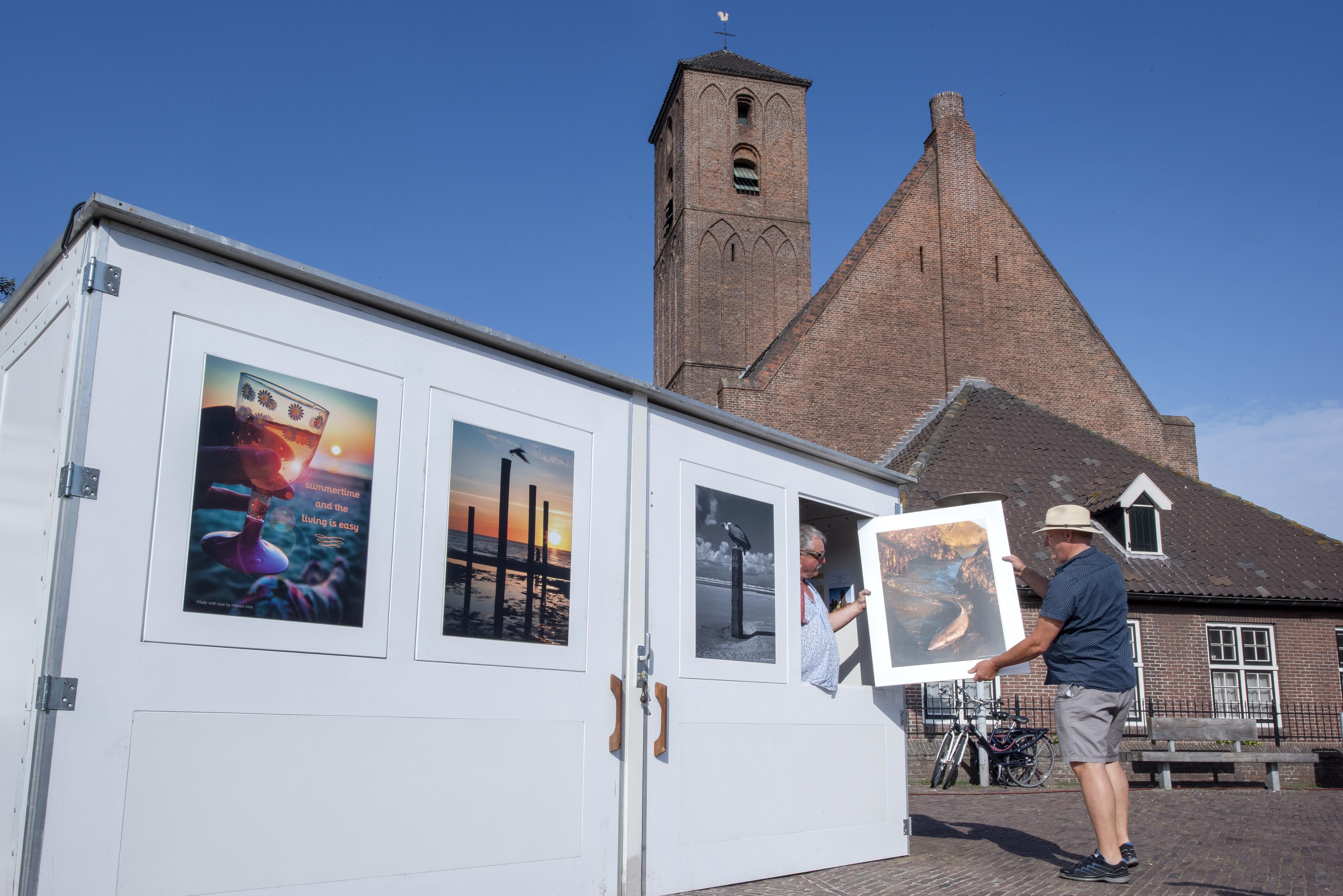 Vishandelaar Bob Vos begint een kunstveiling op zijn kraam in Wijk aan Zee