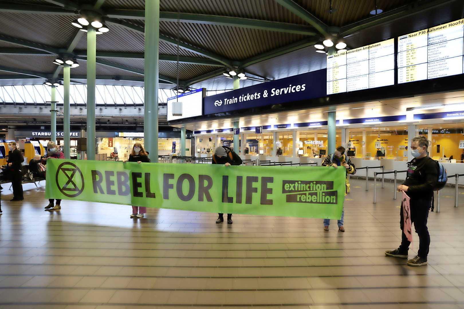 Extinction Rebellion voert actie op Schiphol. Demonstranten hebben zich vastgelijmd aan de incheckbalies, 7 arrestaties