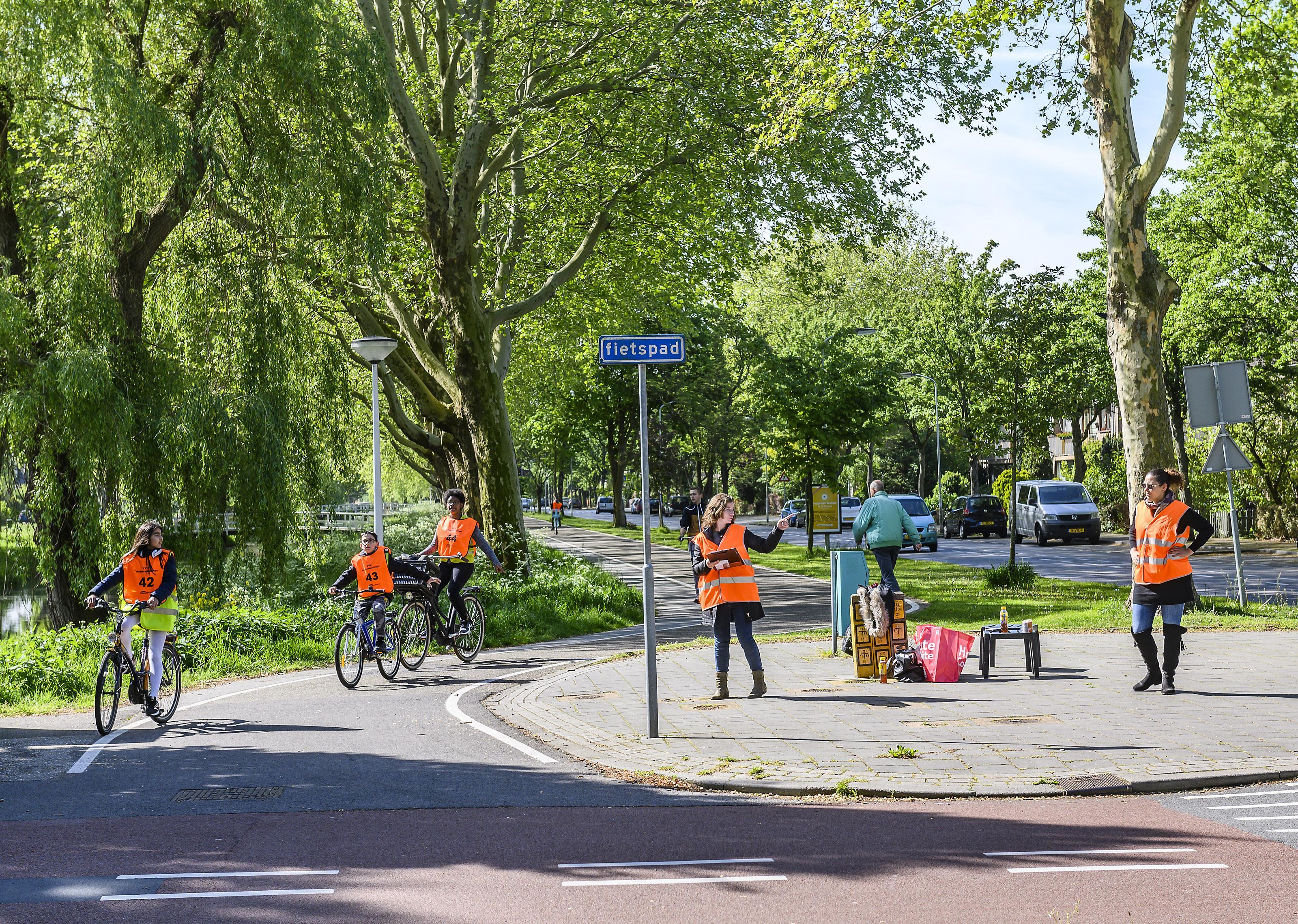Oranje en gele hesjes fietsen door Zaandamse wijken voor verkeersexamen