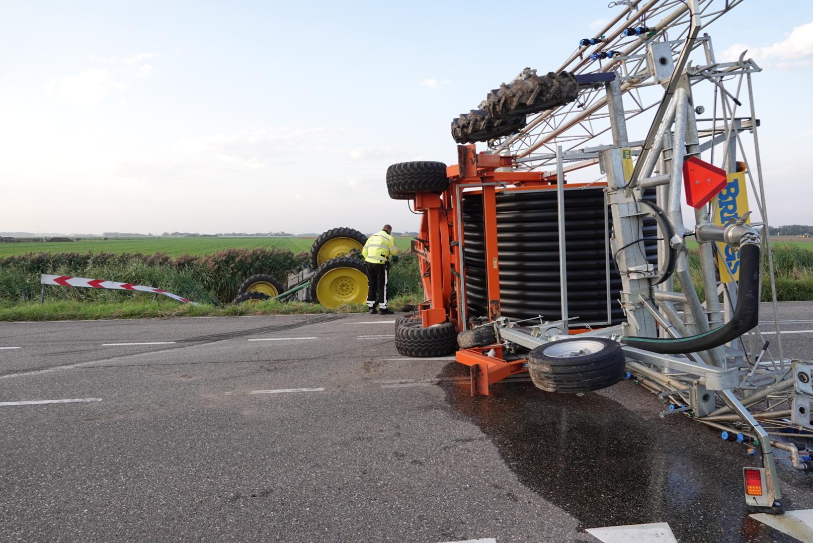Tractor met aanhanger belandt op zijn kant en bijna ondersteboven in water Julianadorp