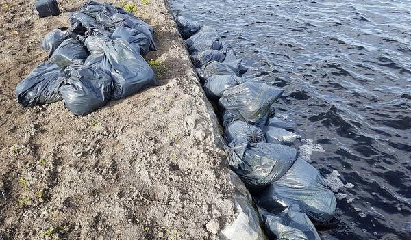 Zakken met drugsafval drijven in water in Warmond