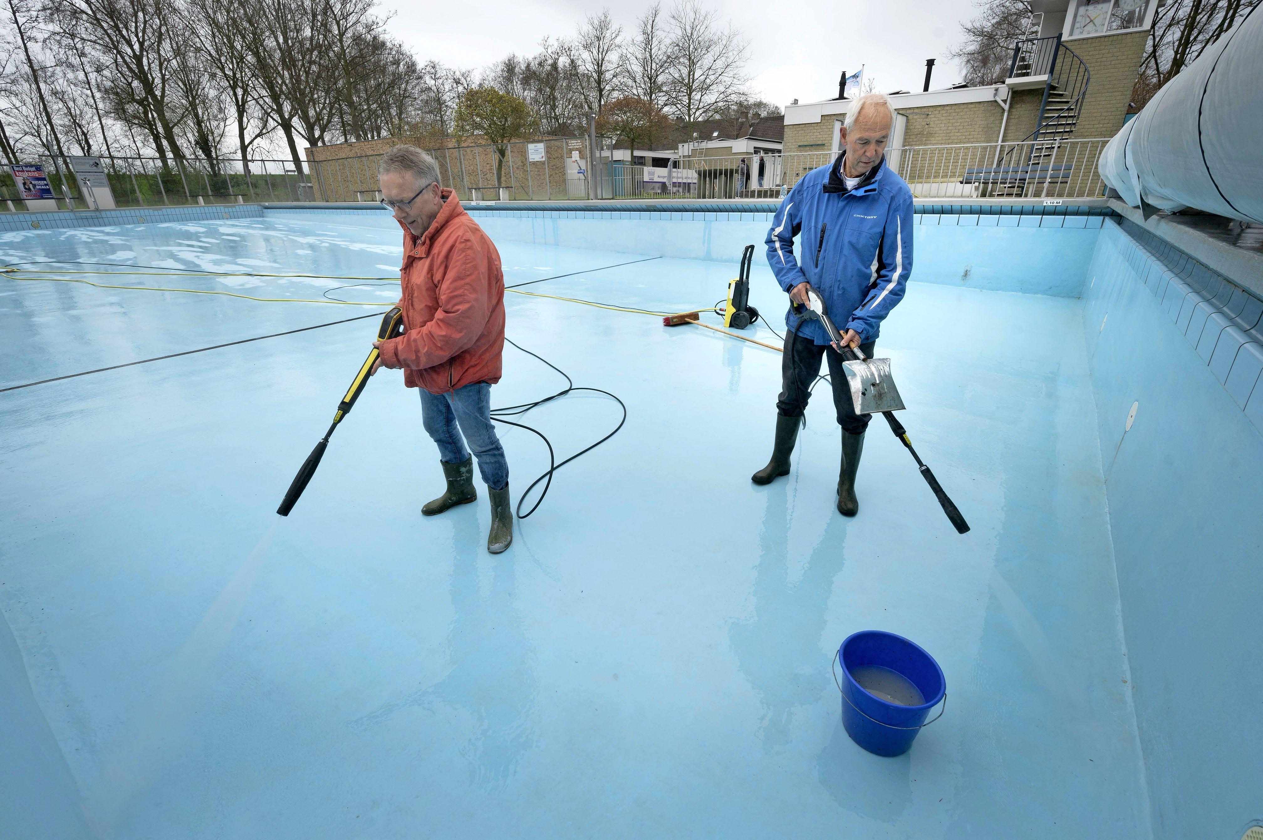 Vrijwilligers schuren het trespa en hanteren de hogedrukspuit: zwembad de Kleine Oase krijgt een grote voorjaarsschoonmaak